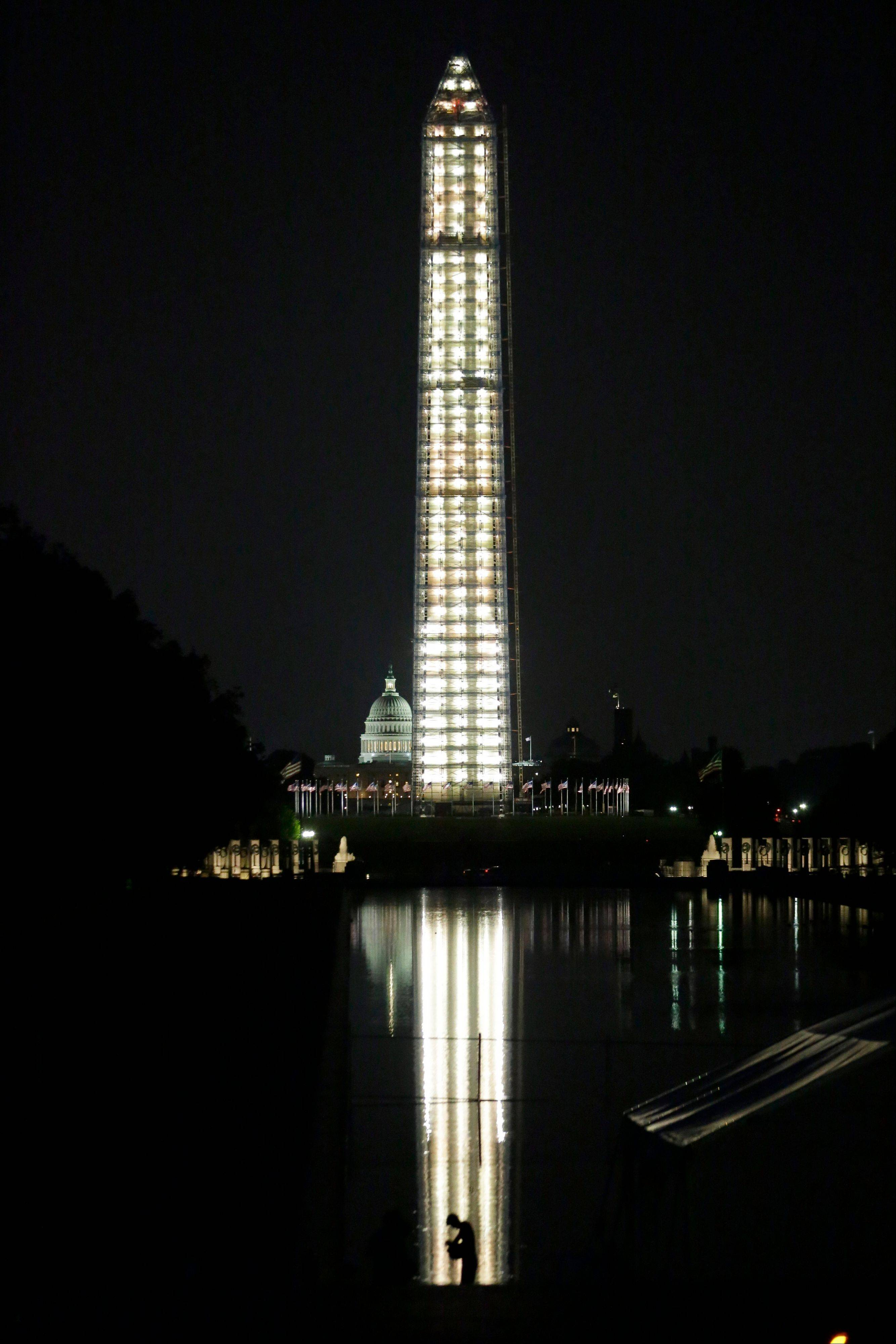 The Washington Monument is lit while undergoing repairs, with the U.S. Capitol behind. The National Park Service will light the monument each night at dusk while it undergoes repairs from the 2011 earthquake. It is expected to reopen in spring of 2014.