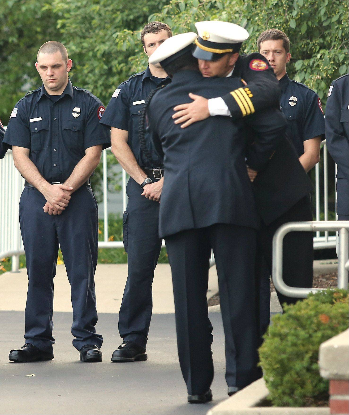 Prescott Battalion Chief Cory Moser, of Arizona, right, hugs another firefighter during the memorial service for Anthony Rose on Thursday at Congdon Funeral Home in Zion. Rose was one of 19 Granite Mountain Hotshots killed June 30 battling a wildfire in Arizona.