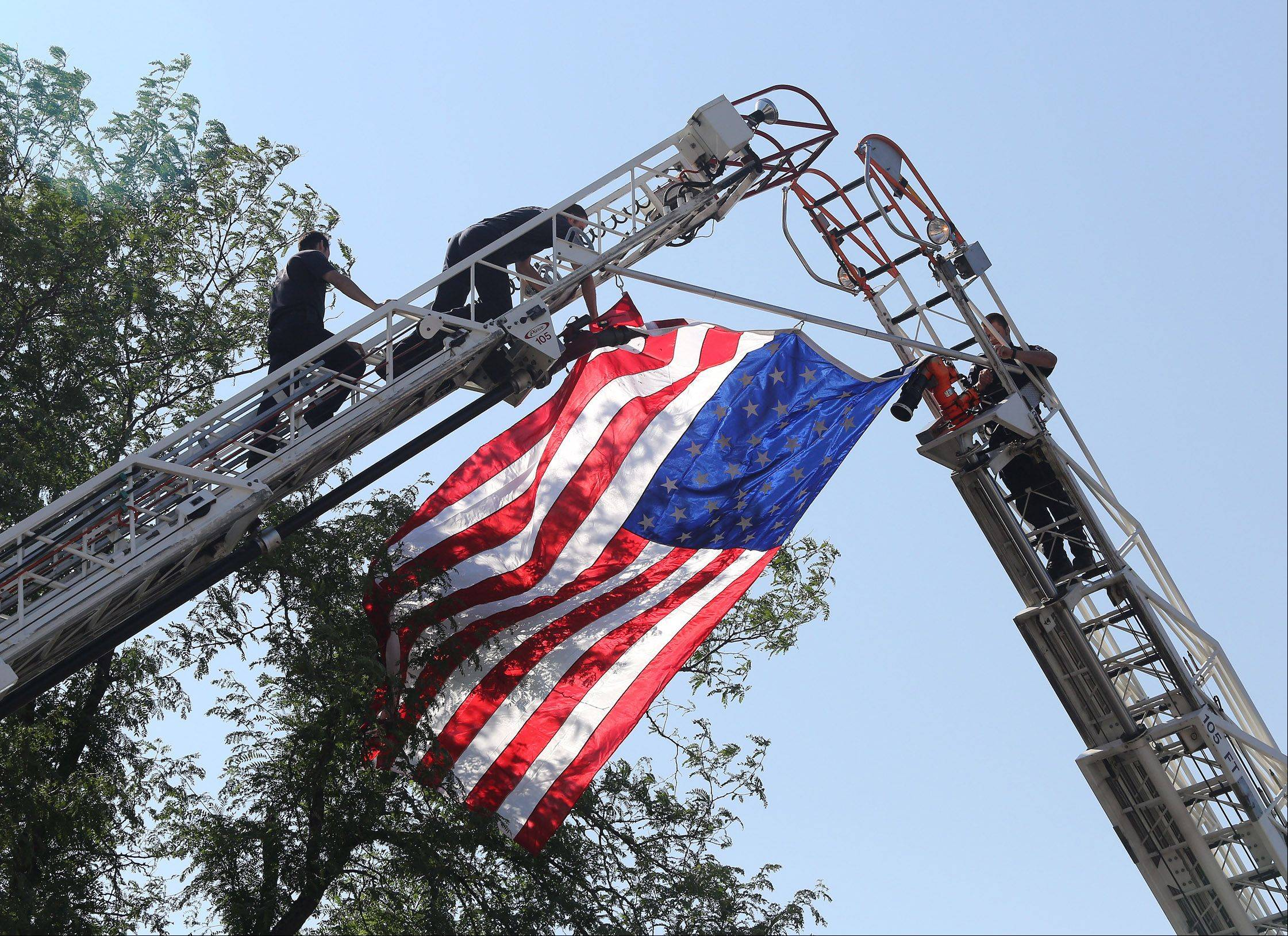 Zion Firefighters display an American flag over the funeral home during the memorial service for Anthony Rose on Thursday at Congdon Funeral Home in Zion. Rose was one of 19 Granite Mountain Hotshots killed June 30 battling a wildfire in Arizona.