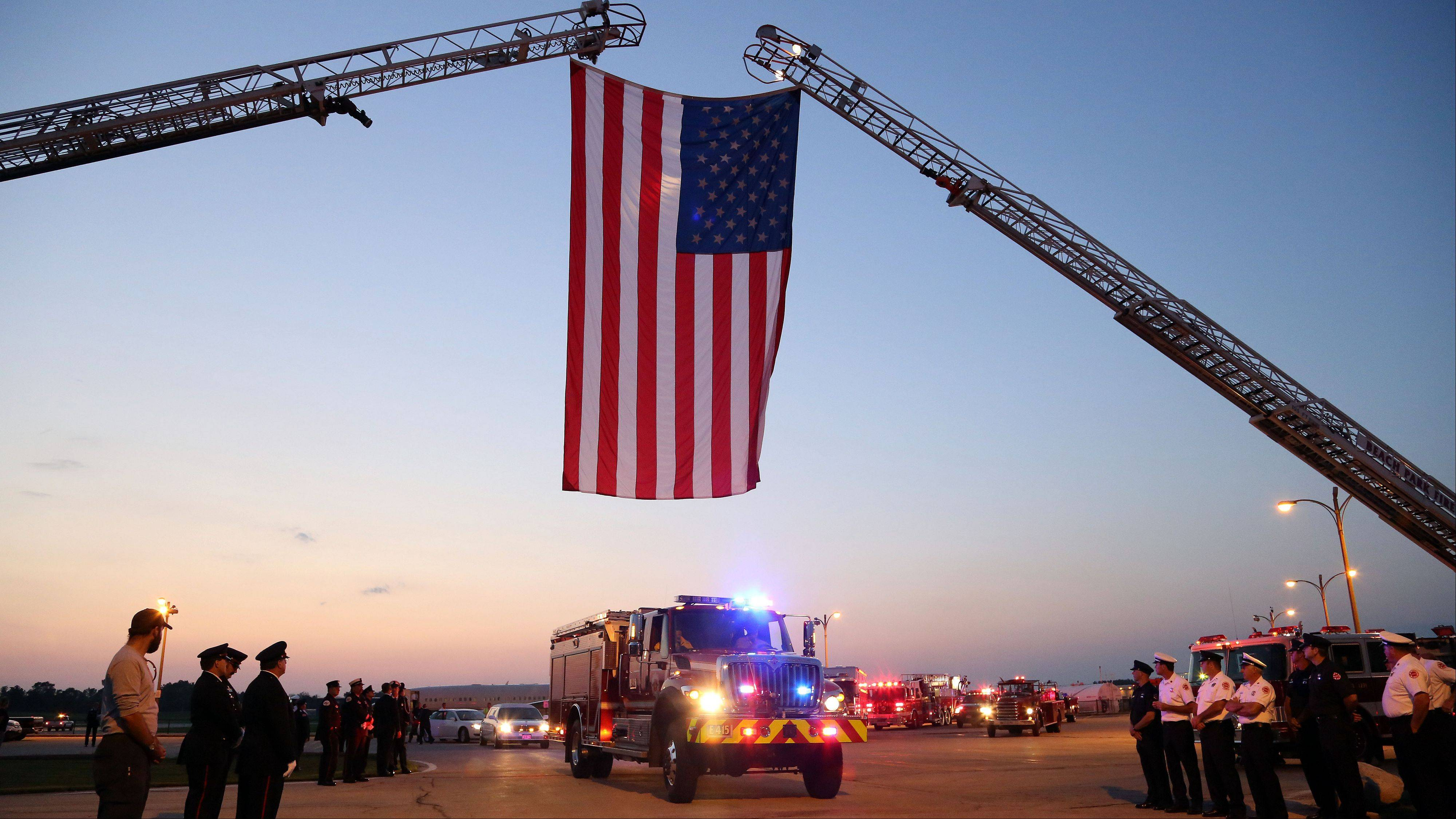 Fire trucks pass under the American flag during a ceremony for Anthony Rose of Beach Park at Waukegan Regional Airport Wednesday night. Rose was killed June 30 along with other members of the Granite Mountain Hotshots while battling a wildfire north of Phoenix.