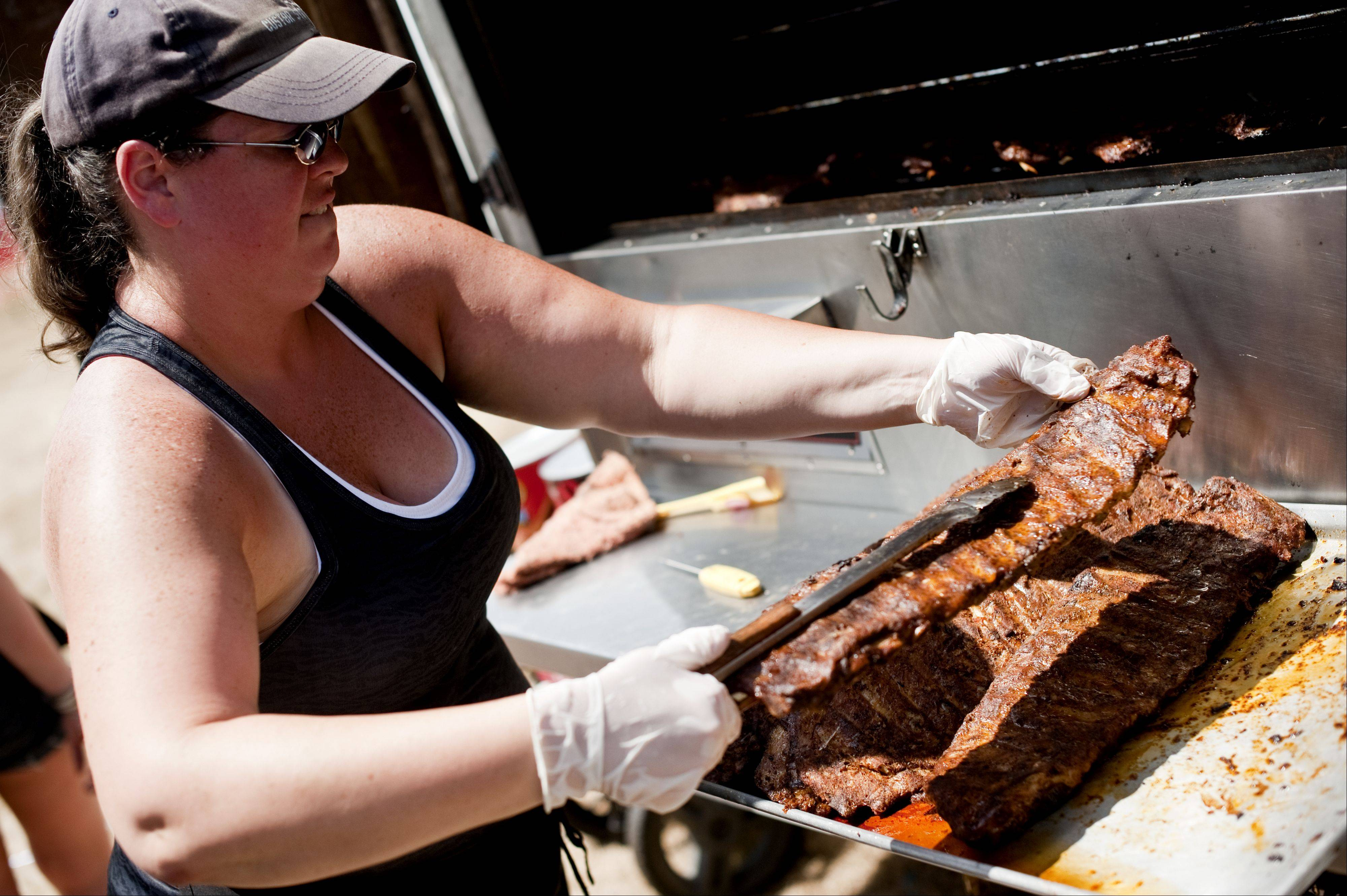 "Katie Hogan of Bolingbrook prepares rib slabs for Uncle Bub's BBQ at last year's Lake in the Hills Rockin' Ribfest in Sunset Park. Uncle Bub's participates in numerous rib fests, showcasing their ribs ""from Reno to Boston,"" according to Hogan."
