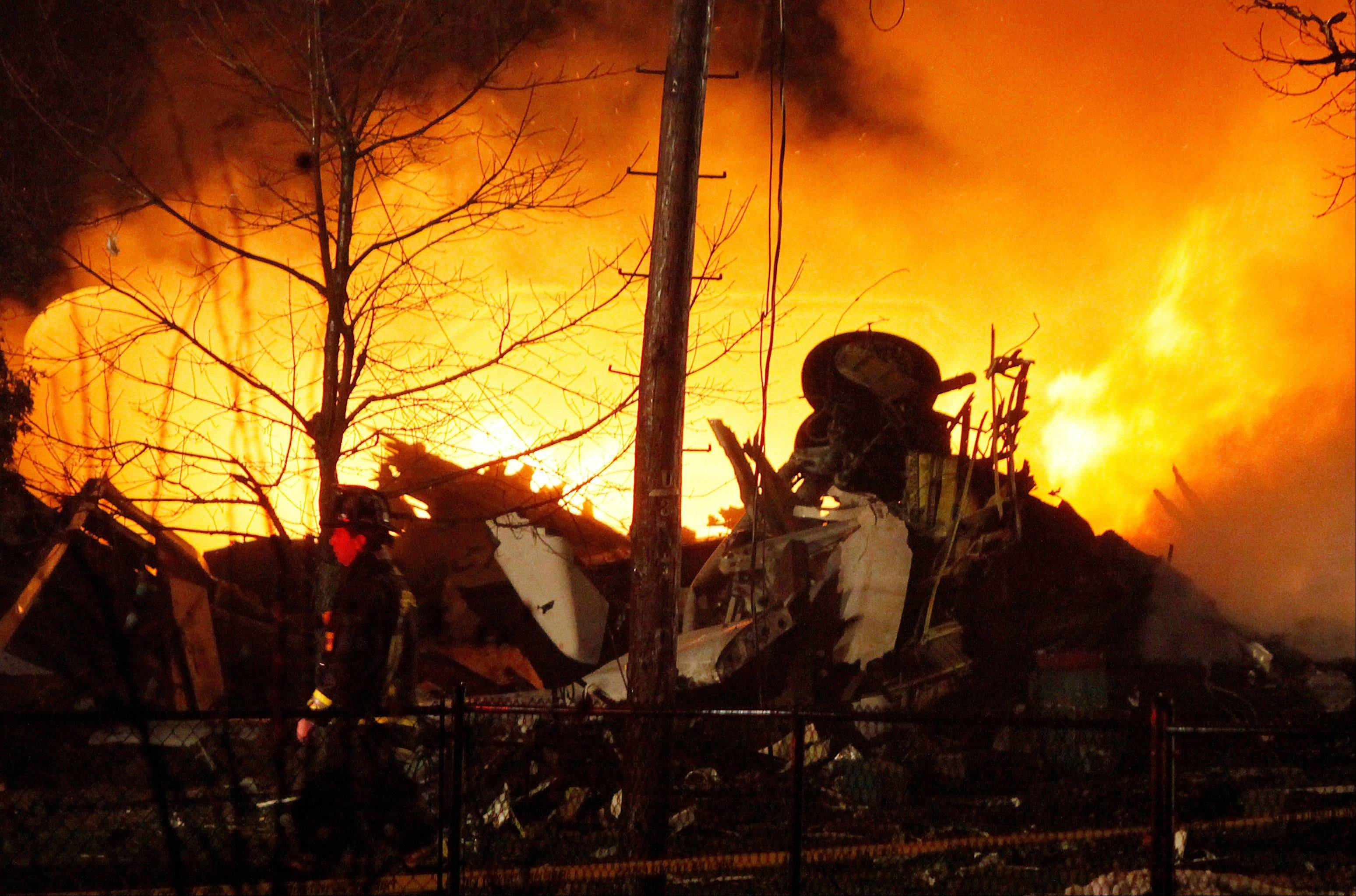 In this Feb. 12, 2009, file photo, a plane burns after it crashed into a house in Clarence Center, N.Y. The amount and type of flying experience first officers -- also known as co-pilots -- must have to qualify to fly for an airline will be significantly increased and expanded under new regulations announced Wednesday by the Federal Aviation Administration.