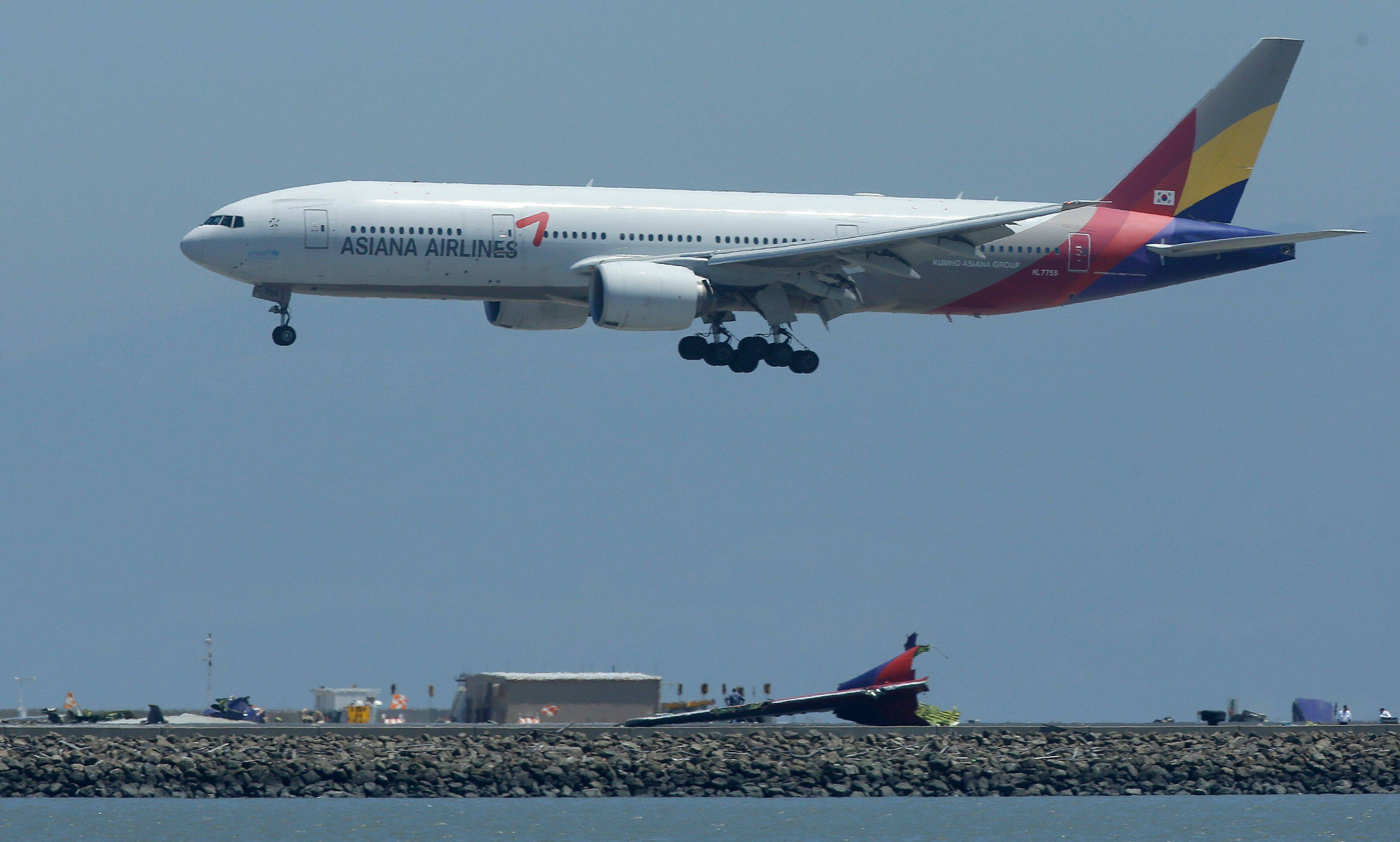 Tuesday's Asiana Flight 214 comes in for a landing over the wreckage of Saturday's Asiana Flight 214 at San Francisco International Airport.