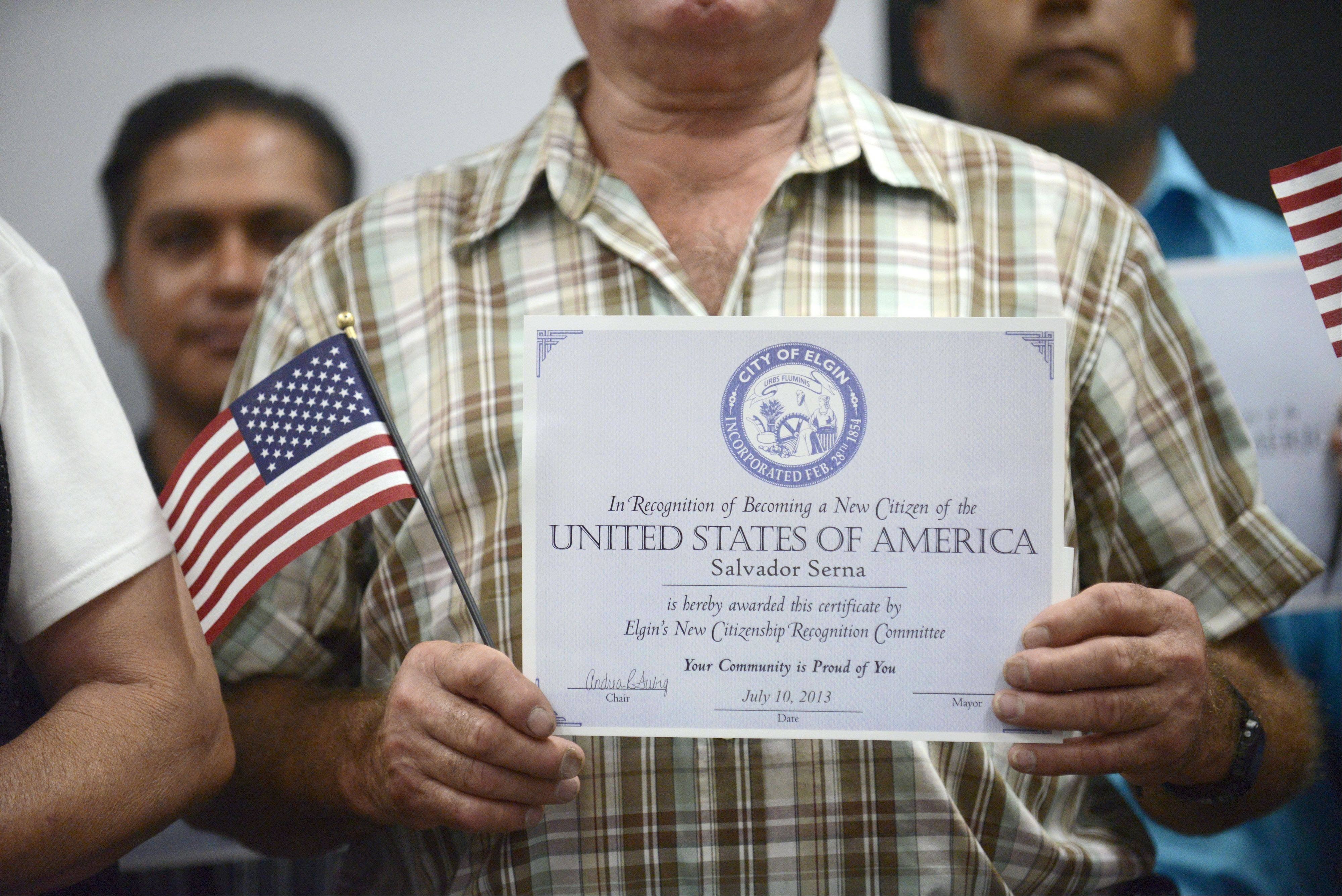"Salvador Serna of Elgin holds up his new citizenship recognition certificate Wednesday during the 15th annual ceremony by the Elgin City Council to recognize new U.S. citizens. Serna said he's been in the United States ""a long, long time."""