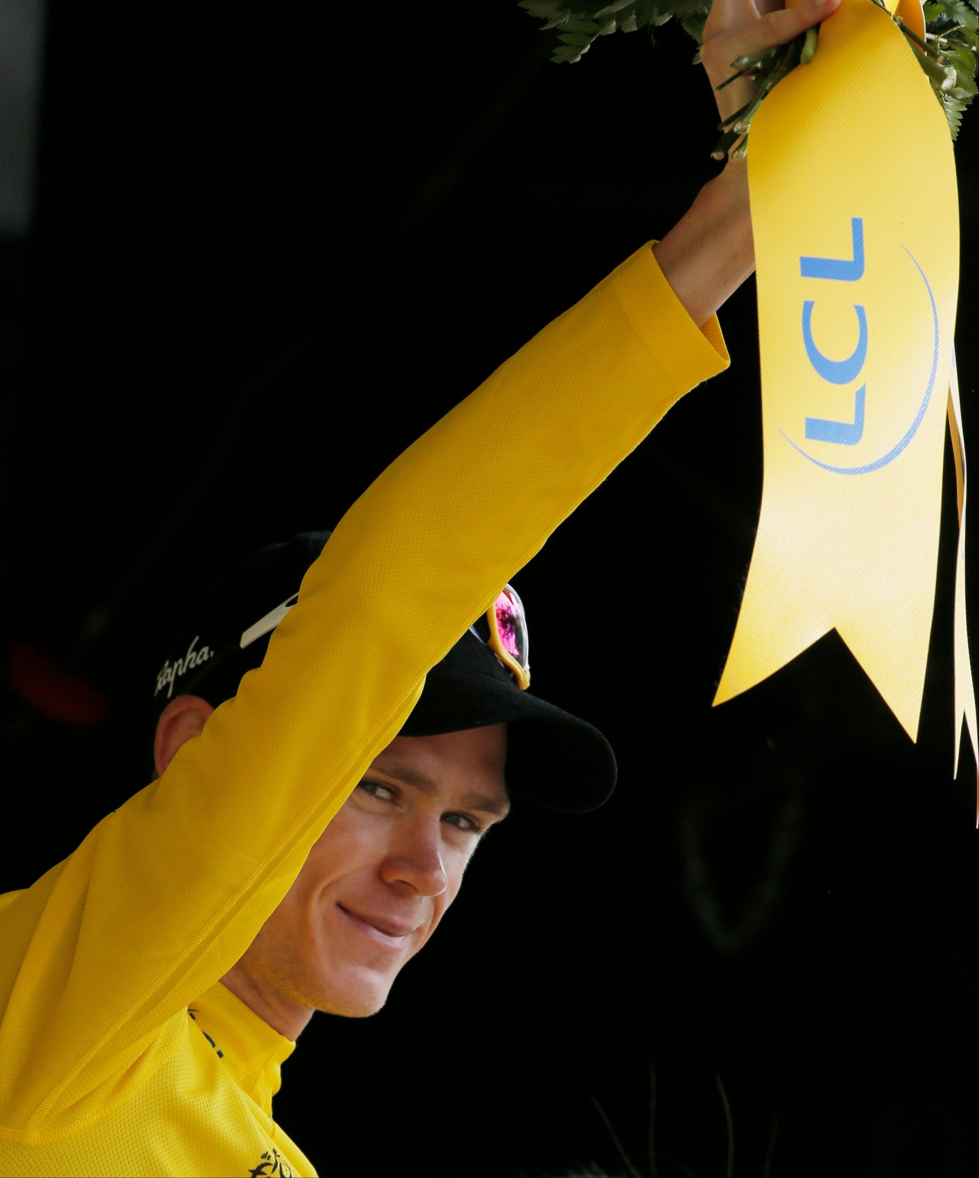 Christopher Froome of Britain, wearing the overall leader's yellow jersey, celebrates on the podium of the twelfth stage of the Tour de France cycling race over 218 kilometers (136.2 miles) with start in in Fougeres and finish in Tours, western France, Thursday July 11 2013. (AP Photo/Laurent Rebours)