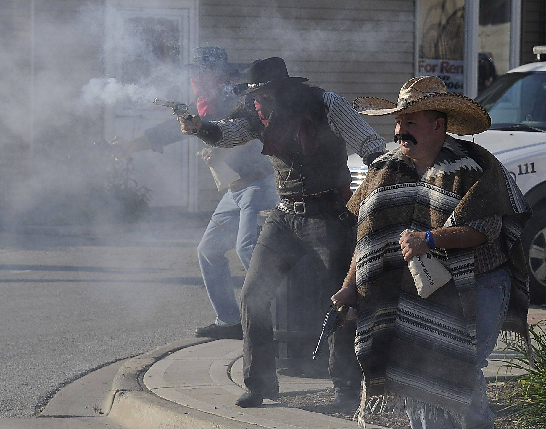 """Bad guys"" Shawn Sponenburg of Lake Geneva, Wis., and John Alvarez of Crystal Lake shoot it out with the law Thursday evening on Main Street to promote the Wauconda rodeo this weekend."