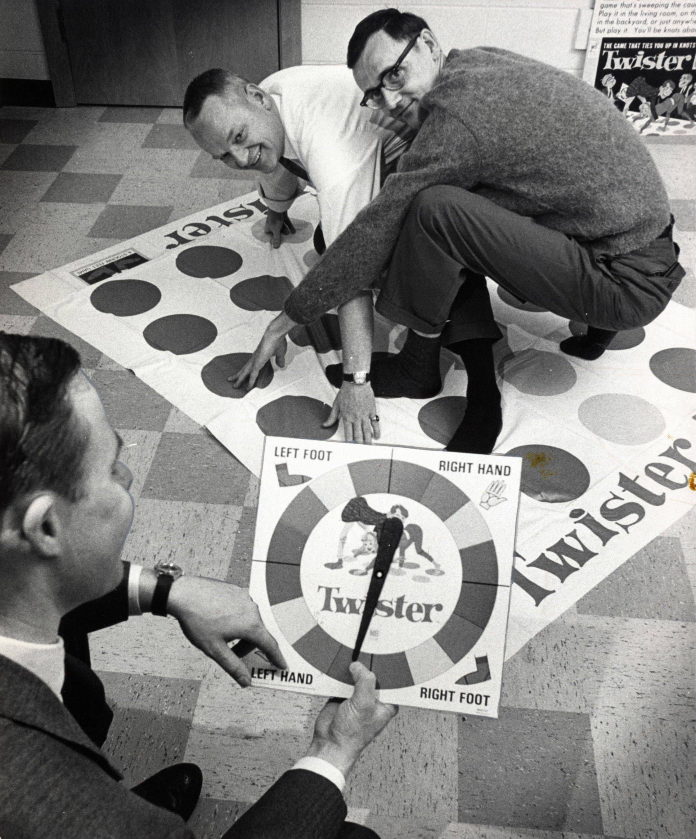 "In a Dec. 16, 1966, photo, co-inventors of the game ""Twister"" Charles Foley, left, and Neil Rabens demonstrate the game for Charles McCarty, foreground, president of Research and Development, Inc., in Minnesota. Foley died Monday at a care facility, according to his son. He was 82."