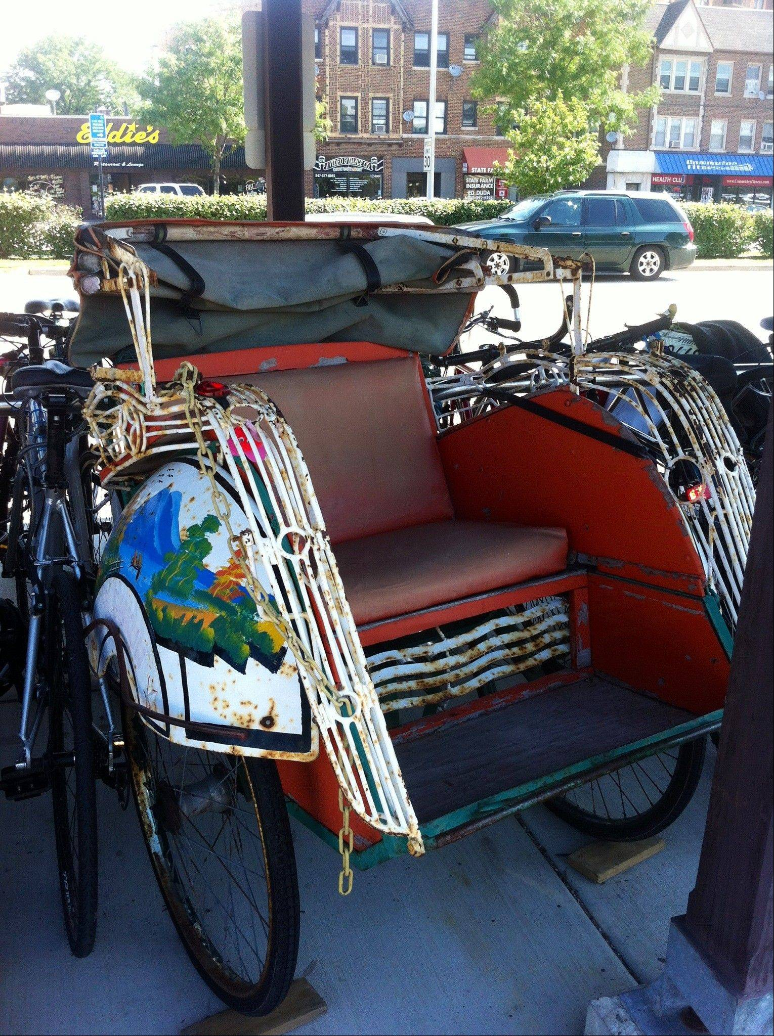The Hi Guy's rickshaw locked up at the downtown Arlington Heights train station.