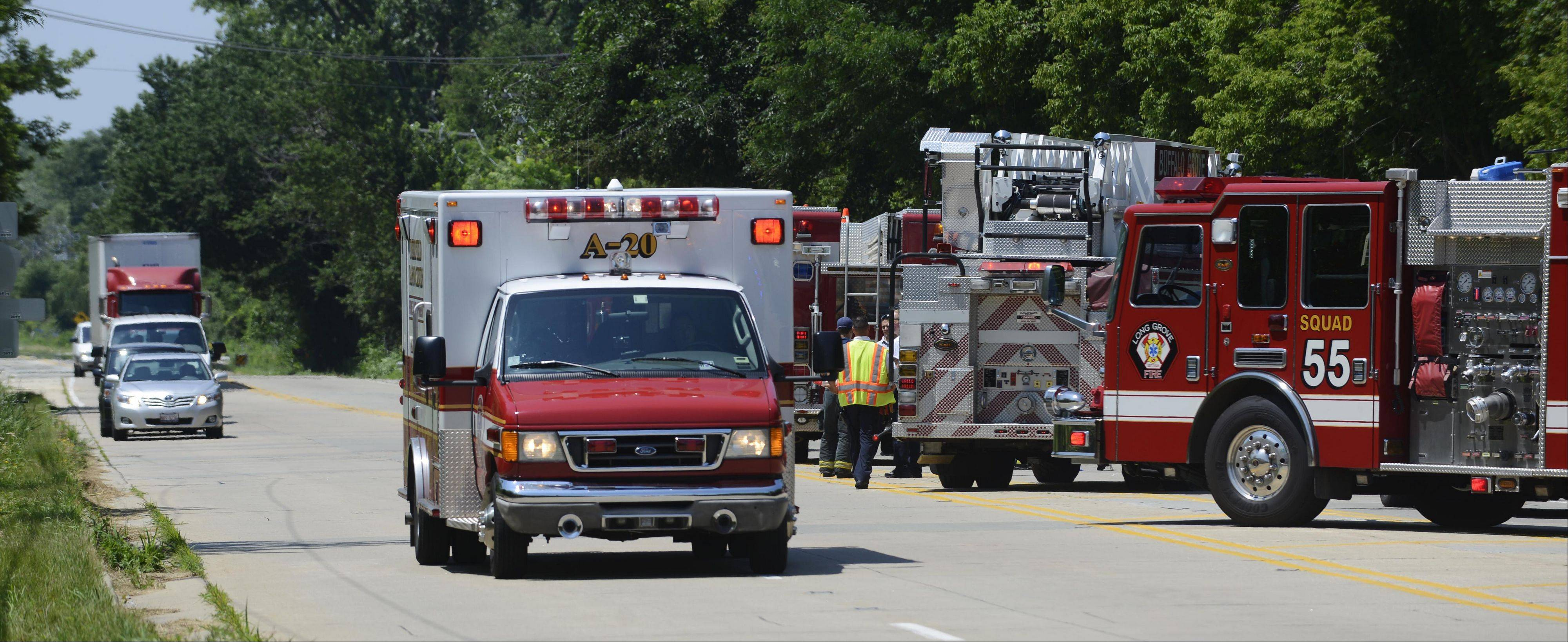 An ambulance departs the scene where two people were rescued Thursday from a 12-foot-deep manhole in Long Grove.