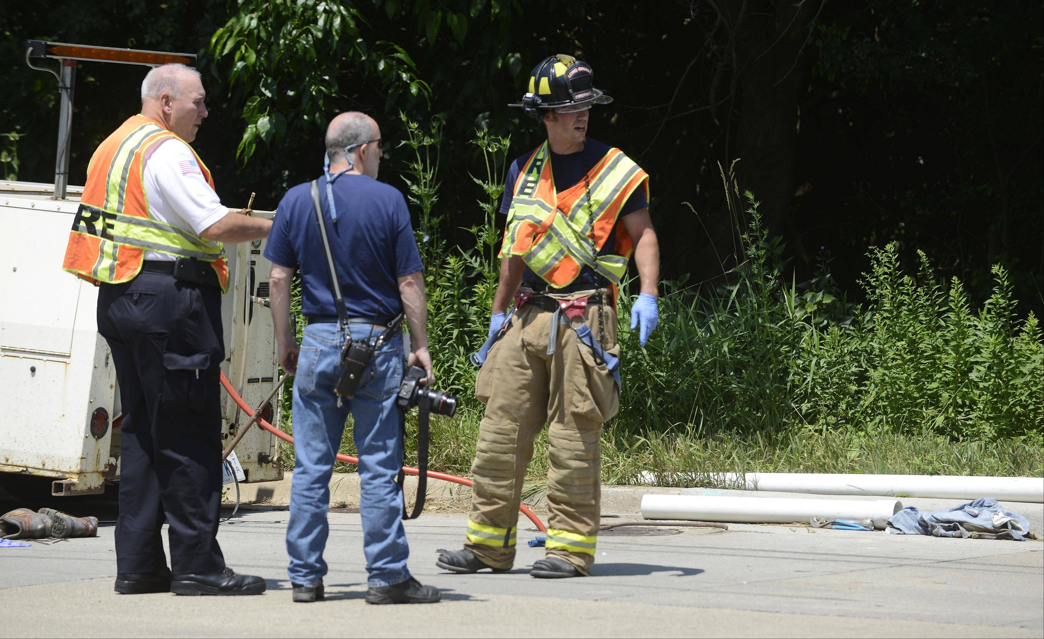 Members of the Long Grove Fire Protection District stand at the scene where two people were rescued from a 12-foot-deep manhole in Long Grove.
