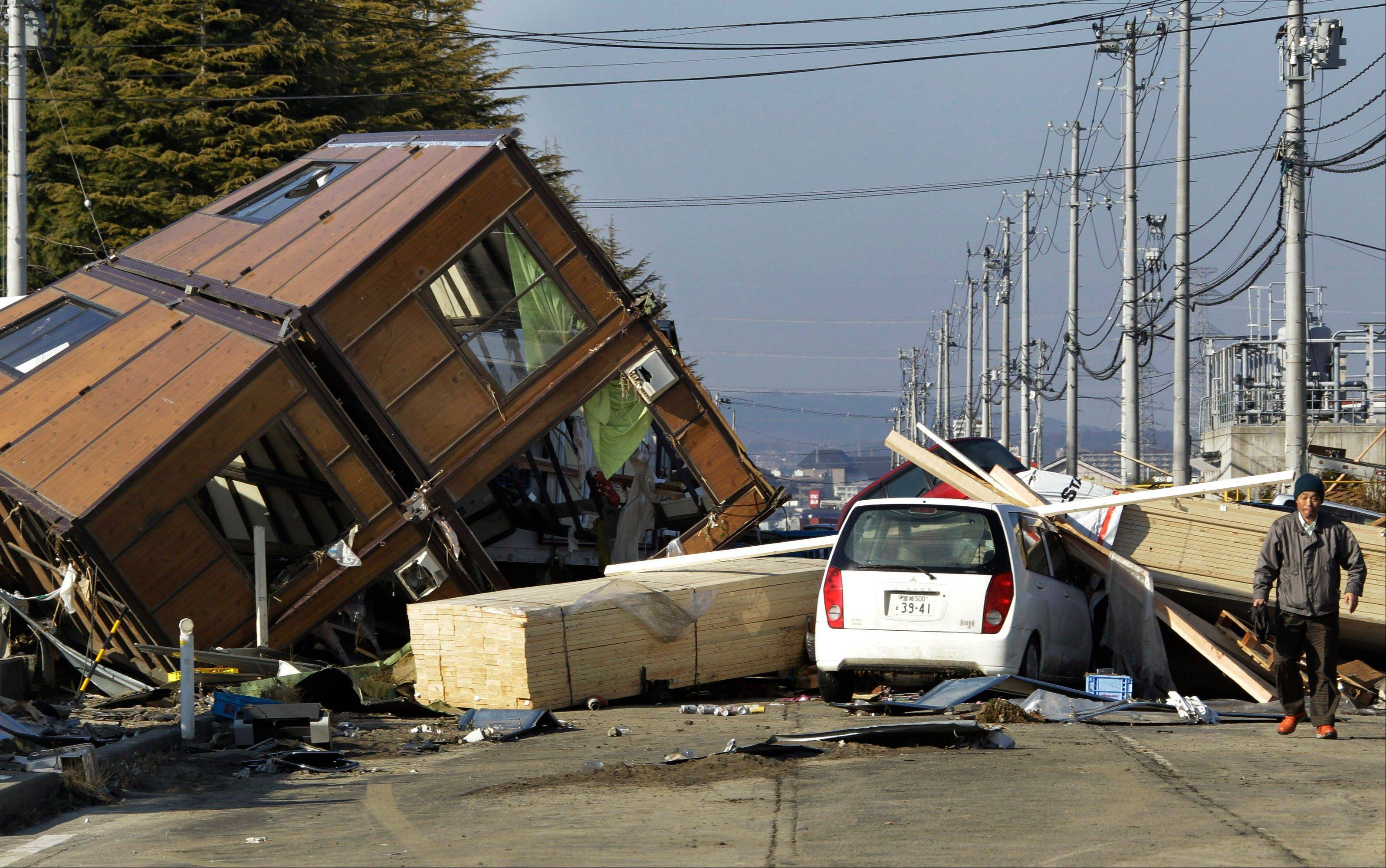 A man walks by a collapsed house and debris in Sendai, northeastern Japan, afterthe devastating 2011 earthquake in Japan. New research appearing Thursday suggests such powerful distant quakes can trigger minor shaking around wastewater injection sites in the U.S. Midwest.