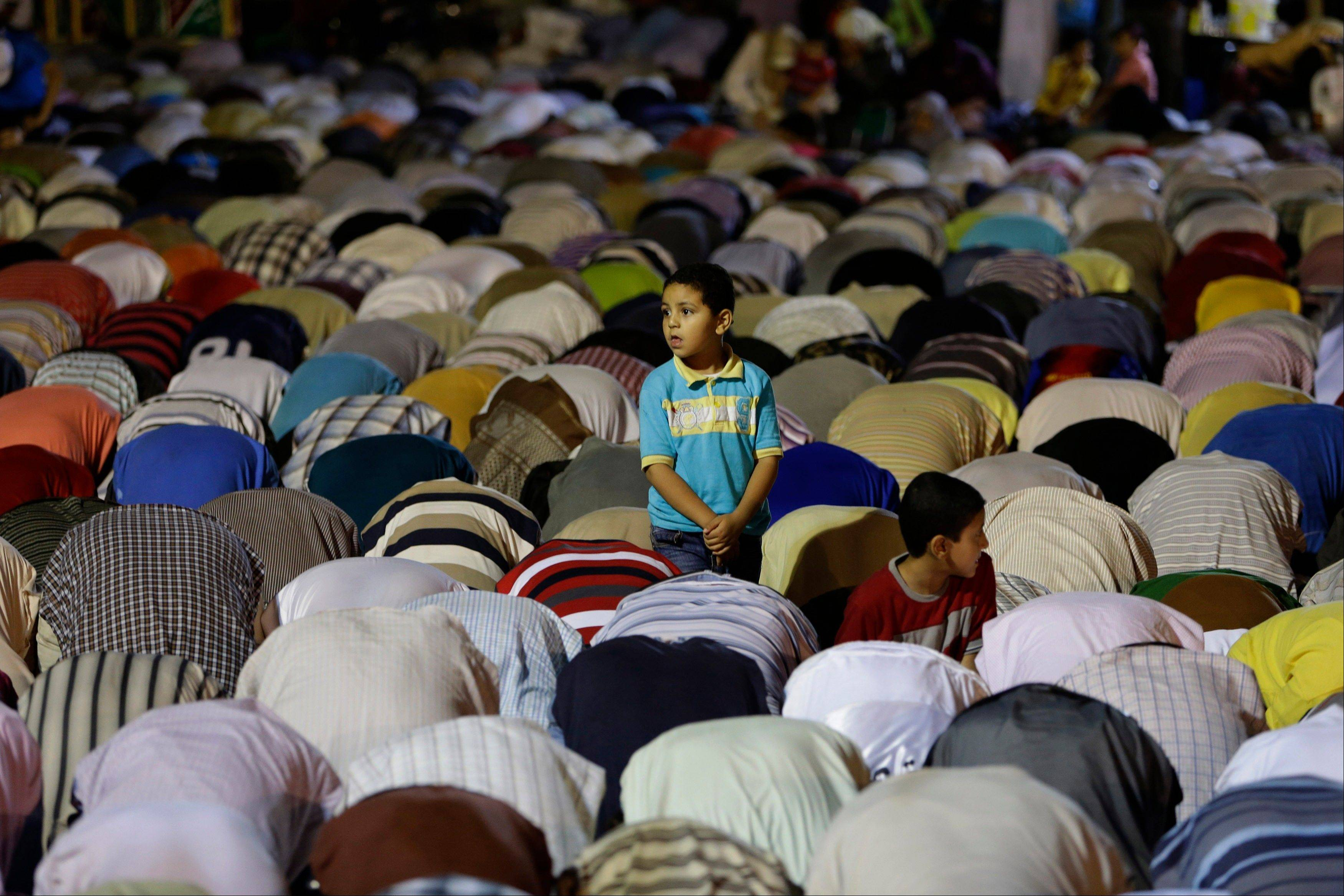 An Egyptian boy stands among the supporters of ousted Egypt's President Mohammed Morsi, who are offering the Tarawih prayer, after the evening meal when Muslims break their fast during the Islamic month of Ramadan, in Nasr City, Cairo, Egypt, Wednesday July 10, 2013.