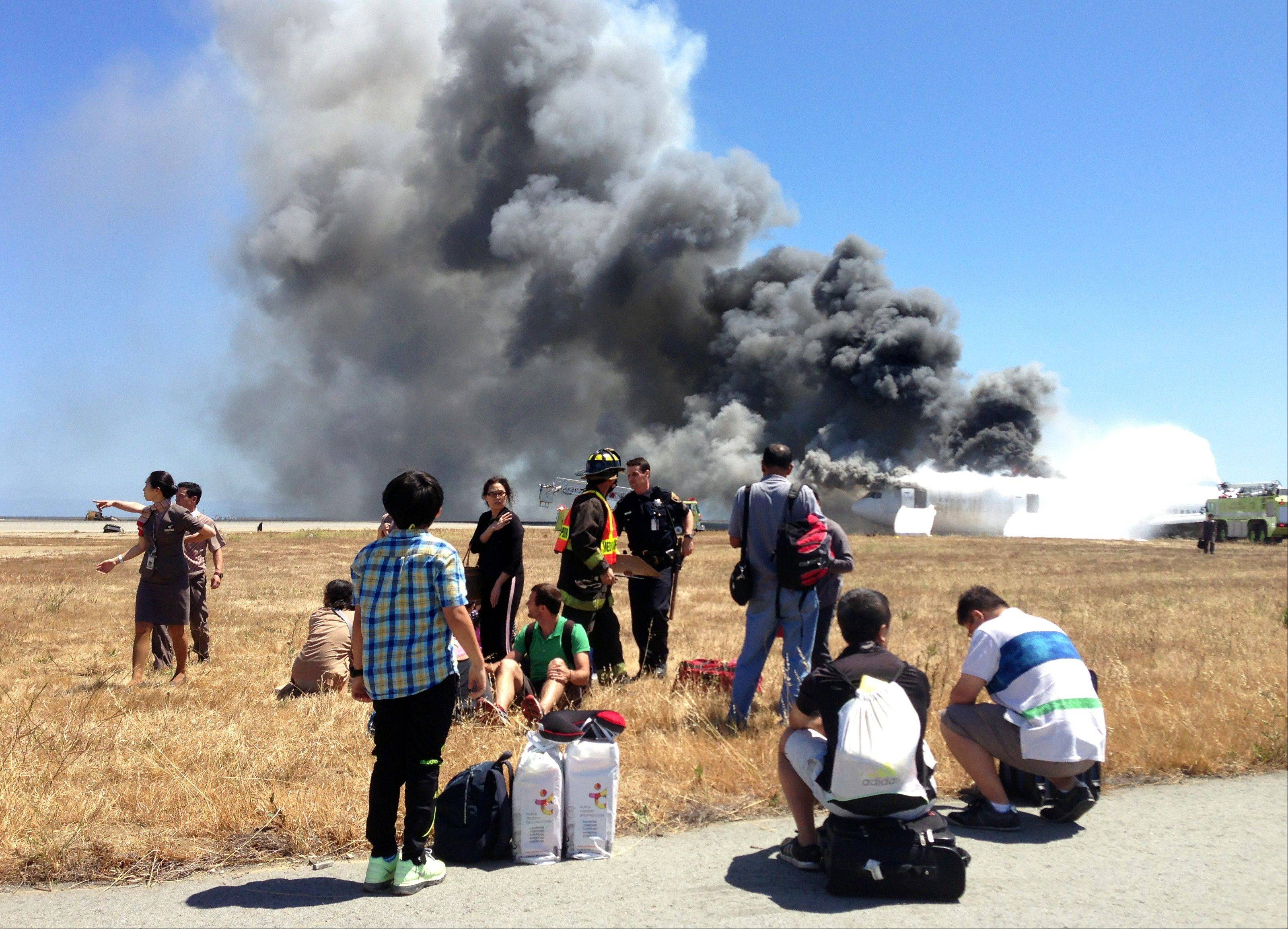 In this photo provided by passenger Benjamin Levy, passengers from Asiana Airlines flight 214, many with their luggage, are seen on the tarmac just moments after the plane crashed at San Francisco International Airport.
