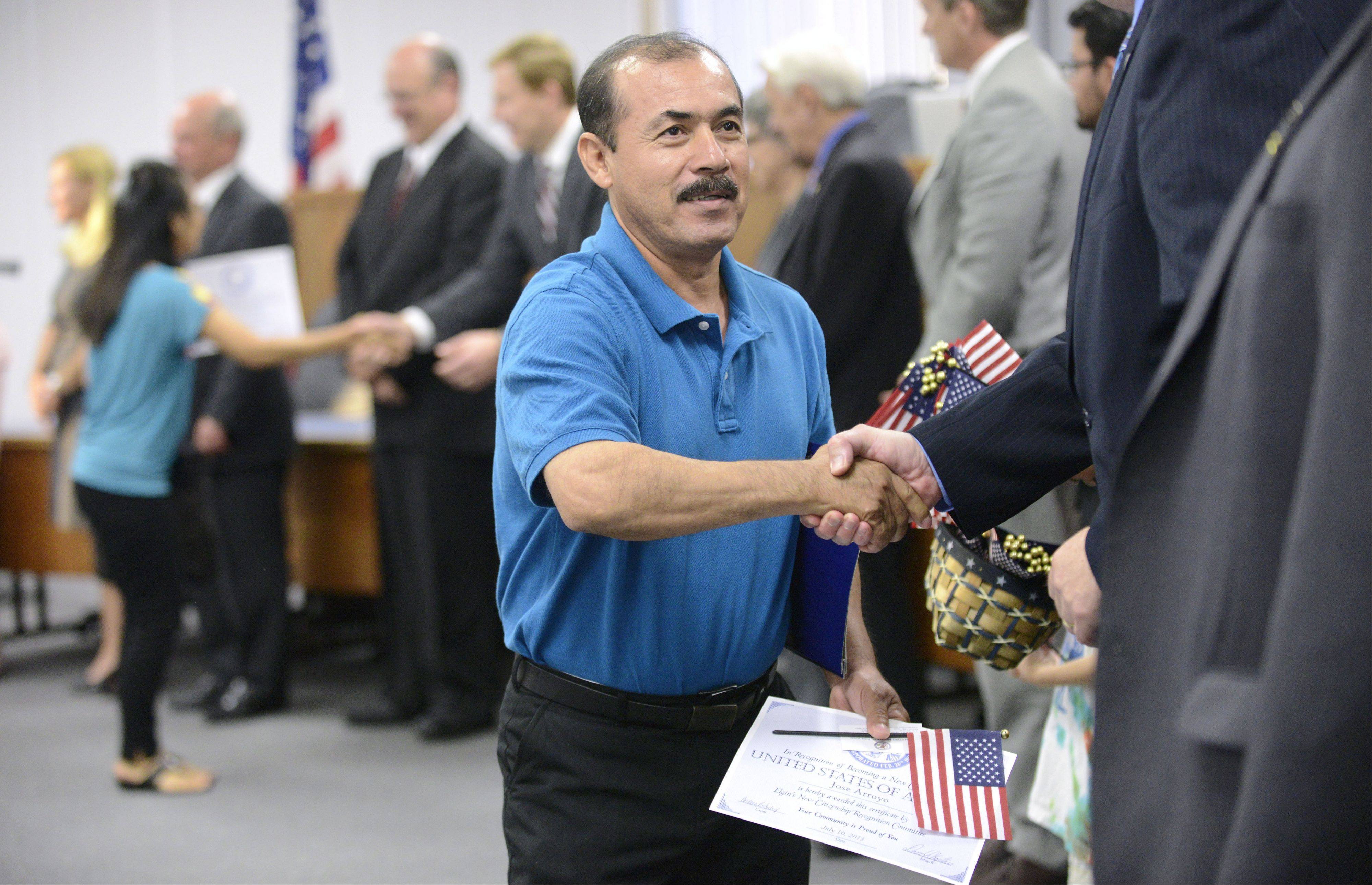 Jose Arroyo, a Streamwood resident originally from Mexico, shakes the hands of Elgin City Council members during the 15th annual new citizenship recognition ceremony Wednesday. Arroyo came from Mexico 10 years ago.