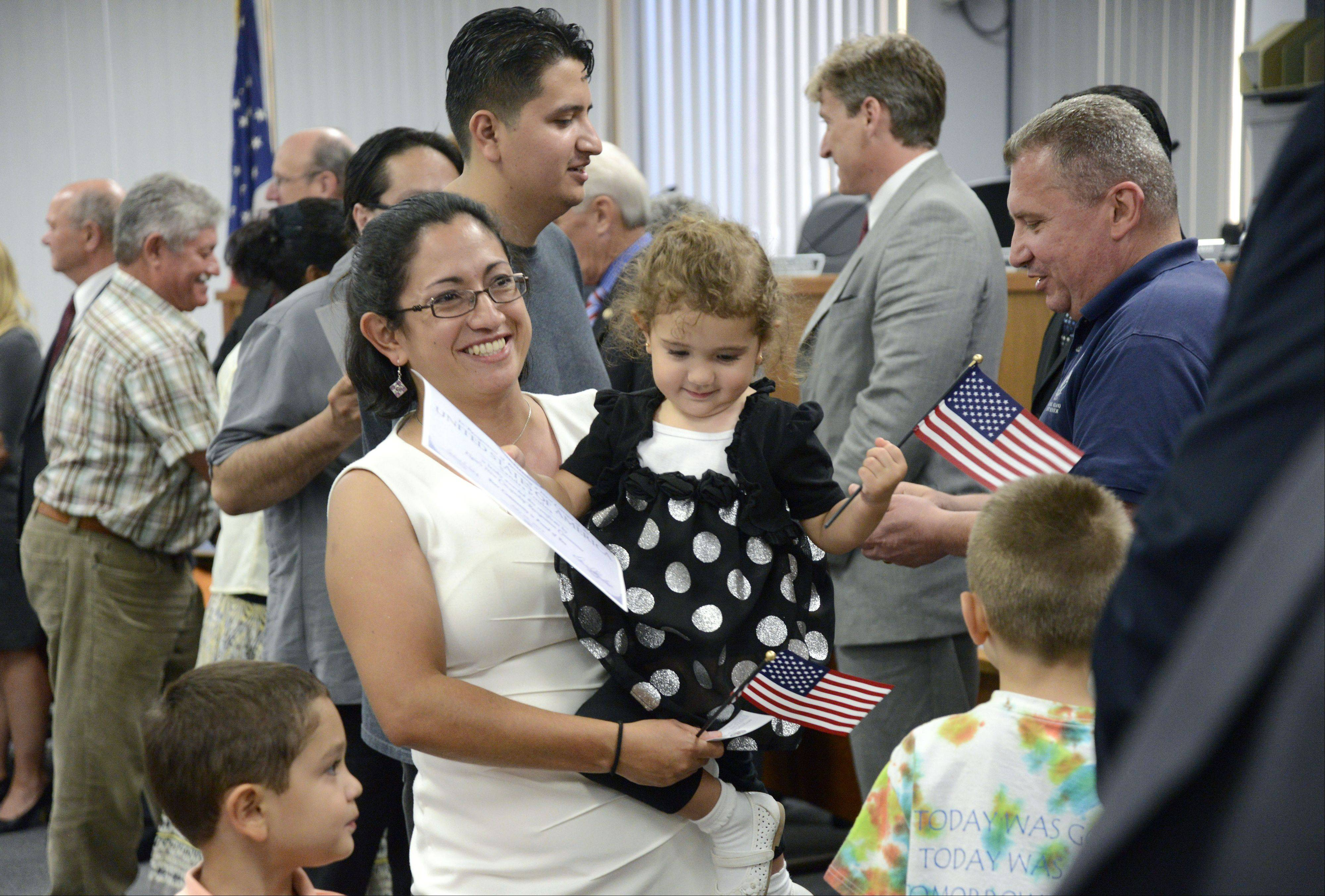 New U.S. citizen Sondra Poulos of West Dundee, a native of Colombia, walks with her son, Andres, 4, and holds her daughter, Marie, 2, during the new citizenship recognition ceremony Wednesday at Elgin city hall.