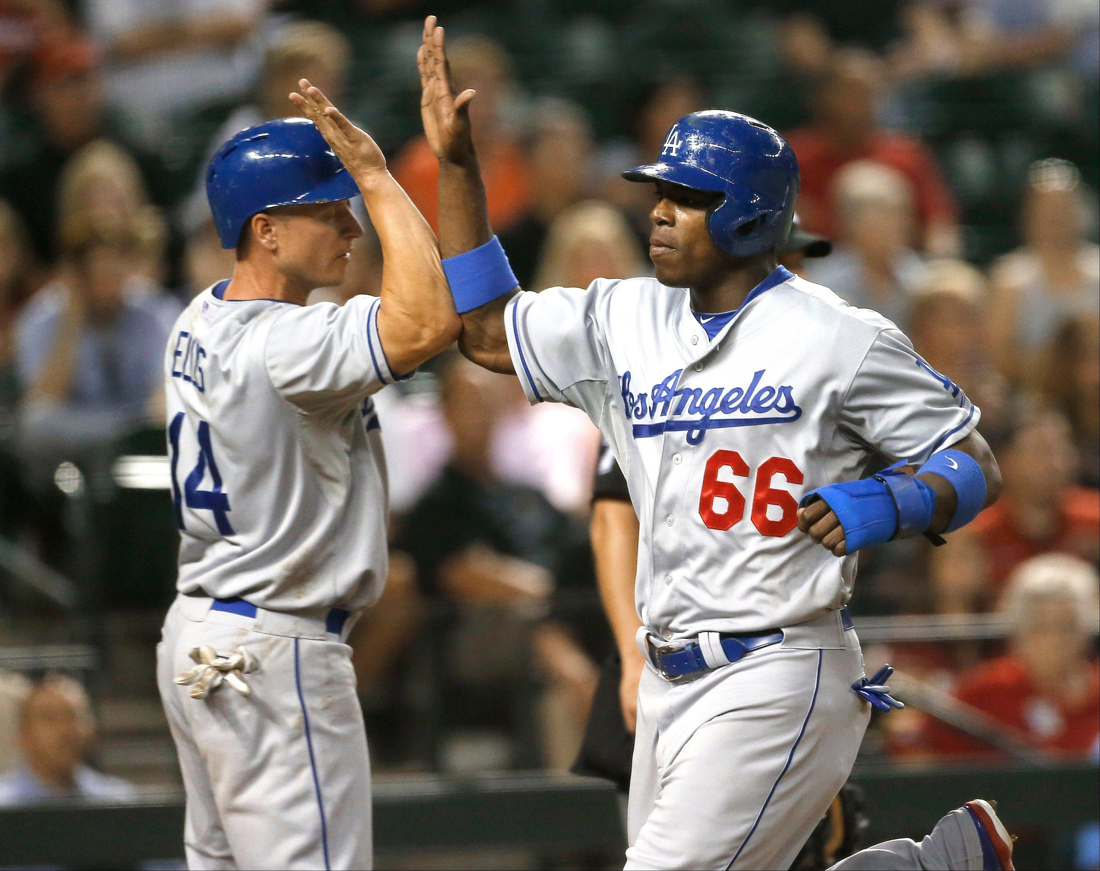 Los Angeles Dodgers' Yasiel Puig (66) and Mark Ellis high-five after scoring on a double by Hanley Ramirez during the fifth inning of a baseball game against the Arizona Diamondbacks, Wednesday, July 10, 2013, in Phoenix.