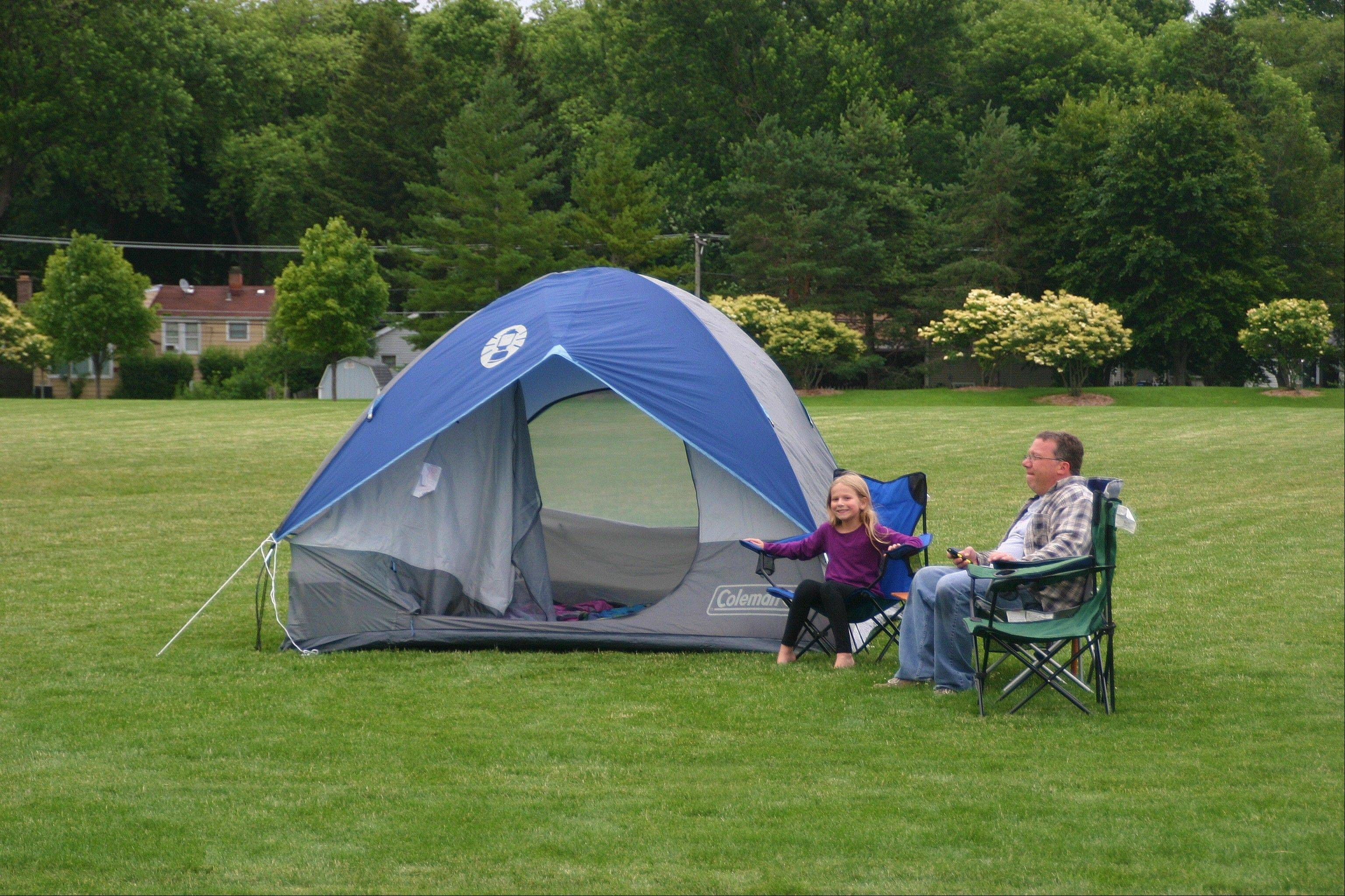 Abigail Heap and her father relax in front of their tent at the second annual Family Campout on June 29-30.