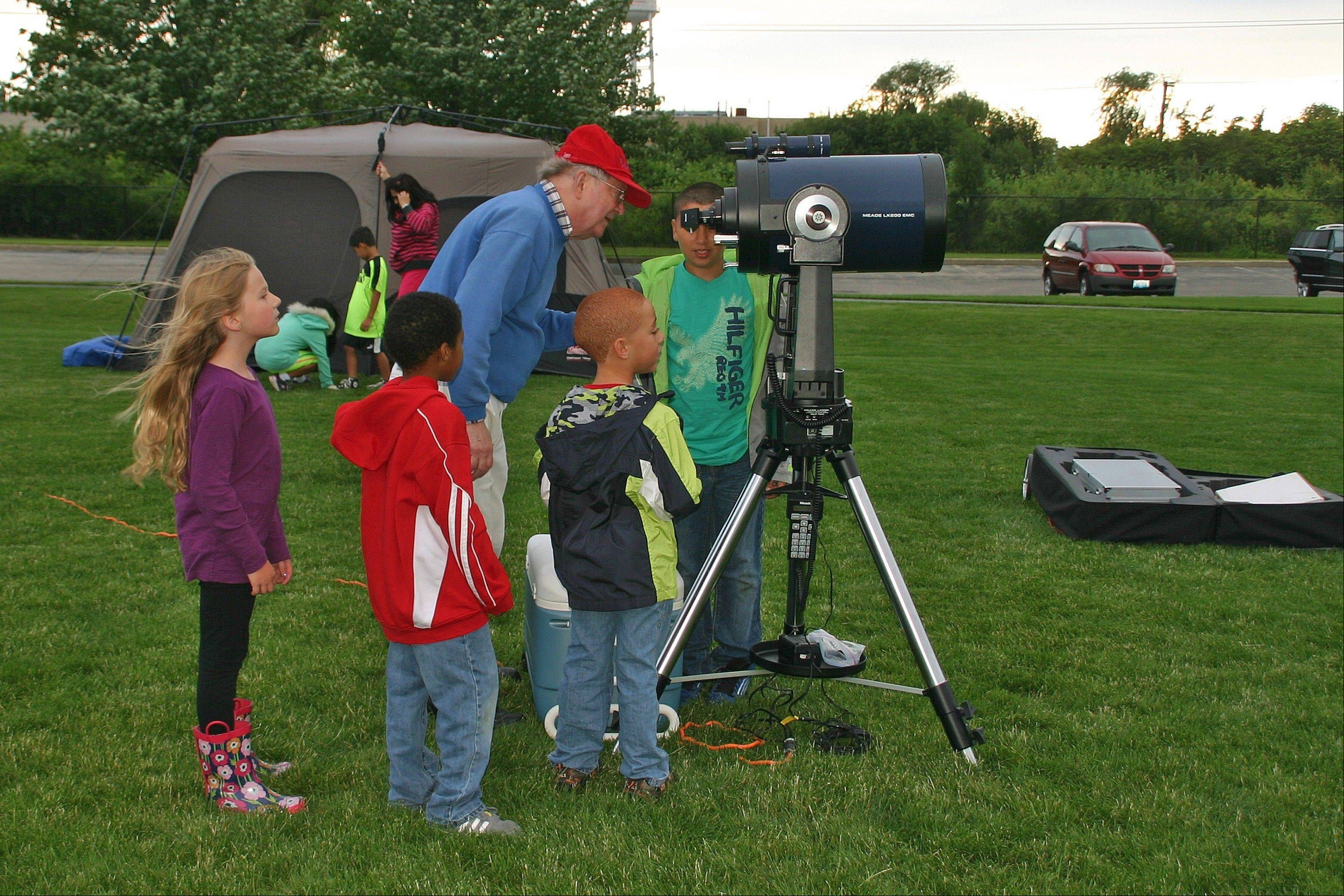 Omar Morris peers at the night sky through the high powered telescope provided courtesy of the Oakton Community College Astronomy Club.