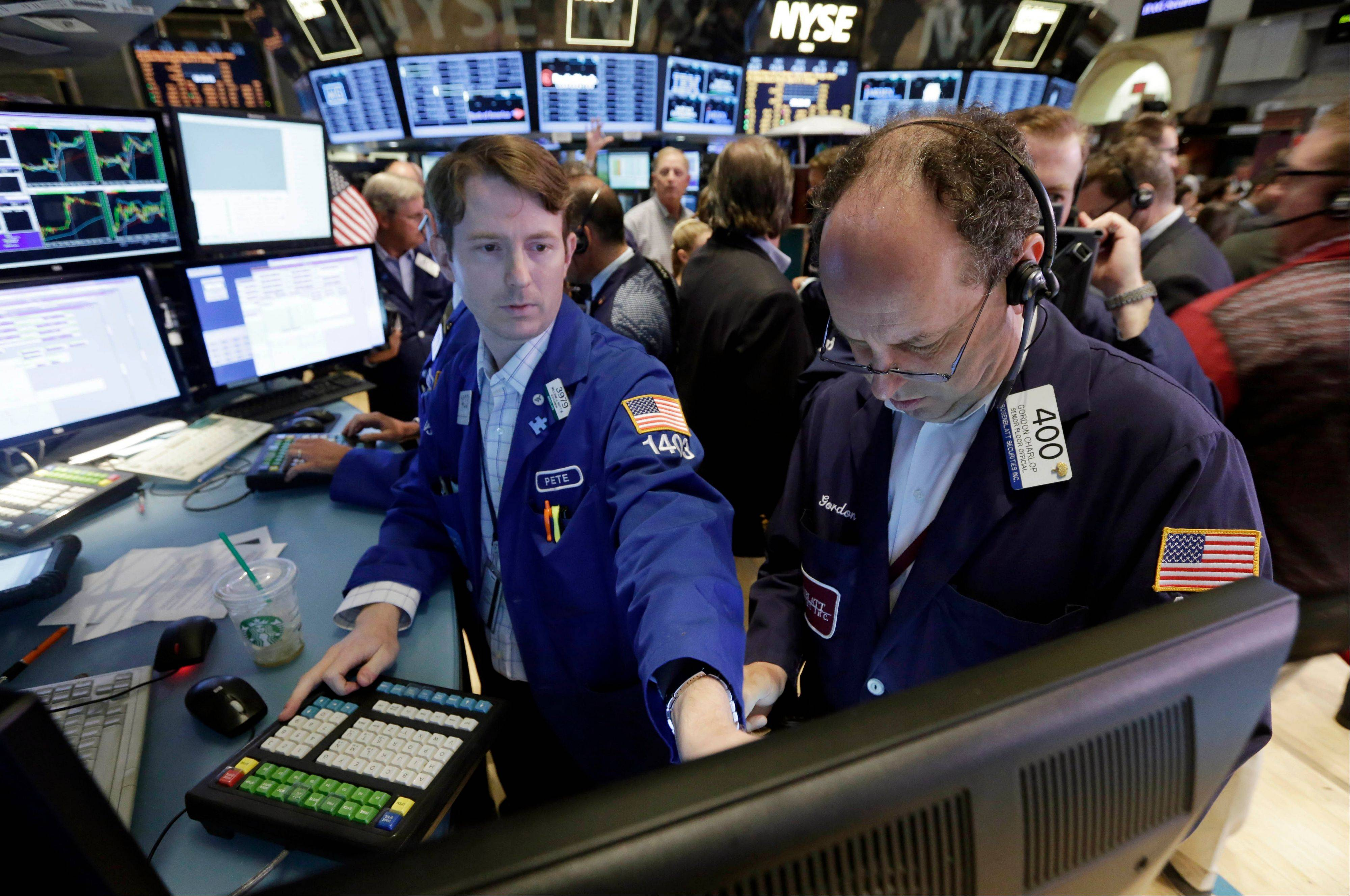 Specialist Peter Elkins, left, and trader Gordon Charlop work Friday on the floor of the New York Stock Exchange.