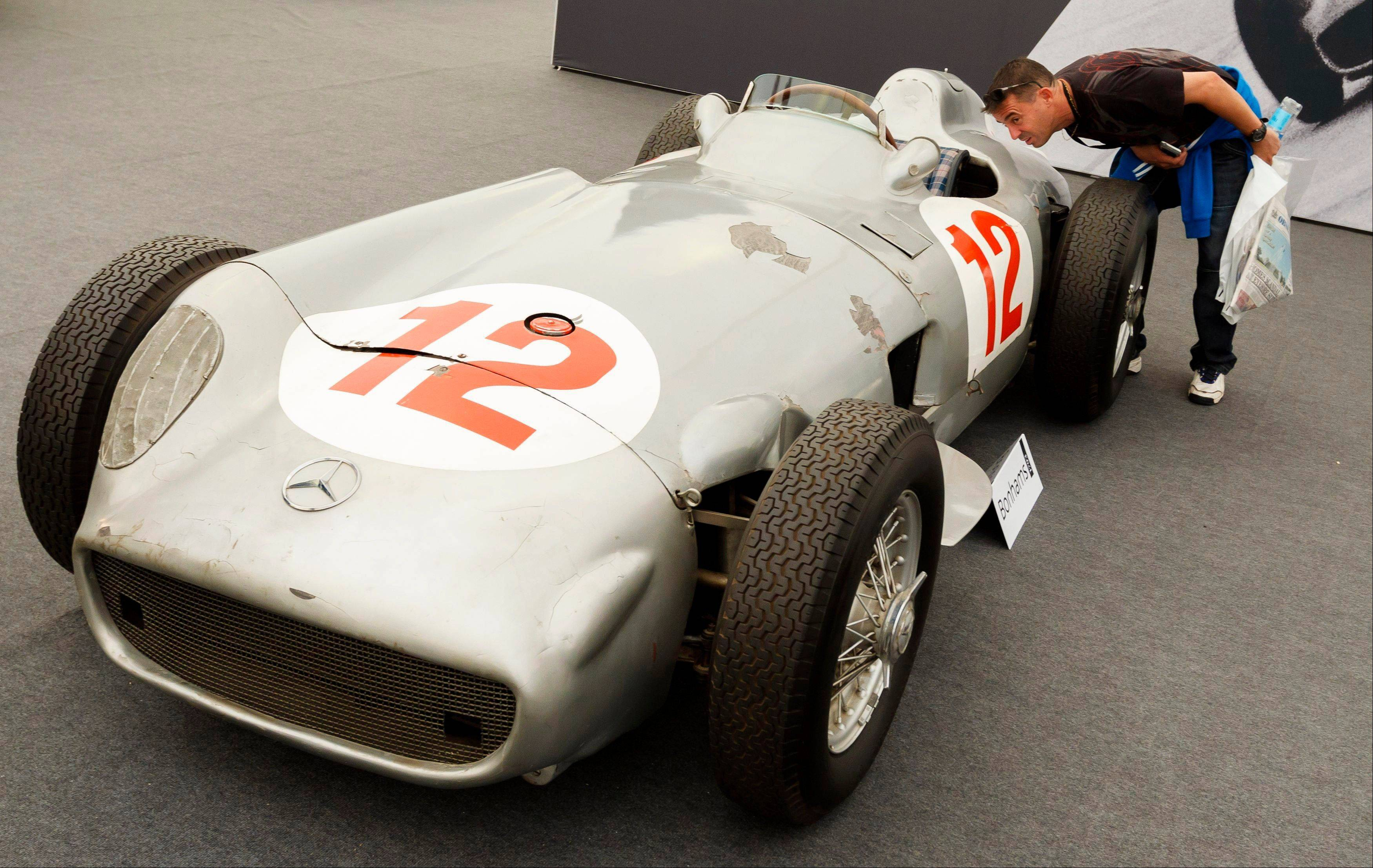 A man looks inside a 1954 Mercedes-Benz W196 single-seater race car Thursday that was once driven by Formula One legend Juan Manuel Fangio, as it is displayed by an auction house at the Festival of Speed in Goodwood, near Chichester, England.