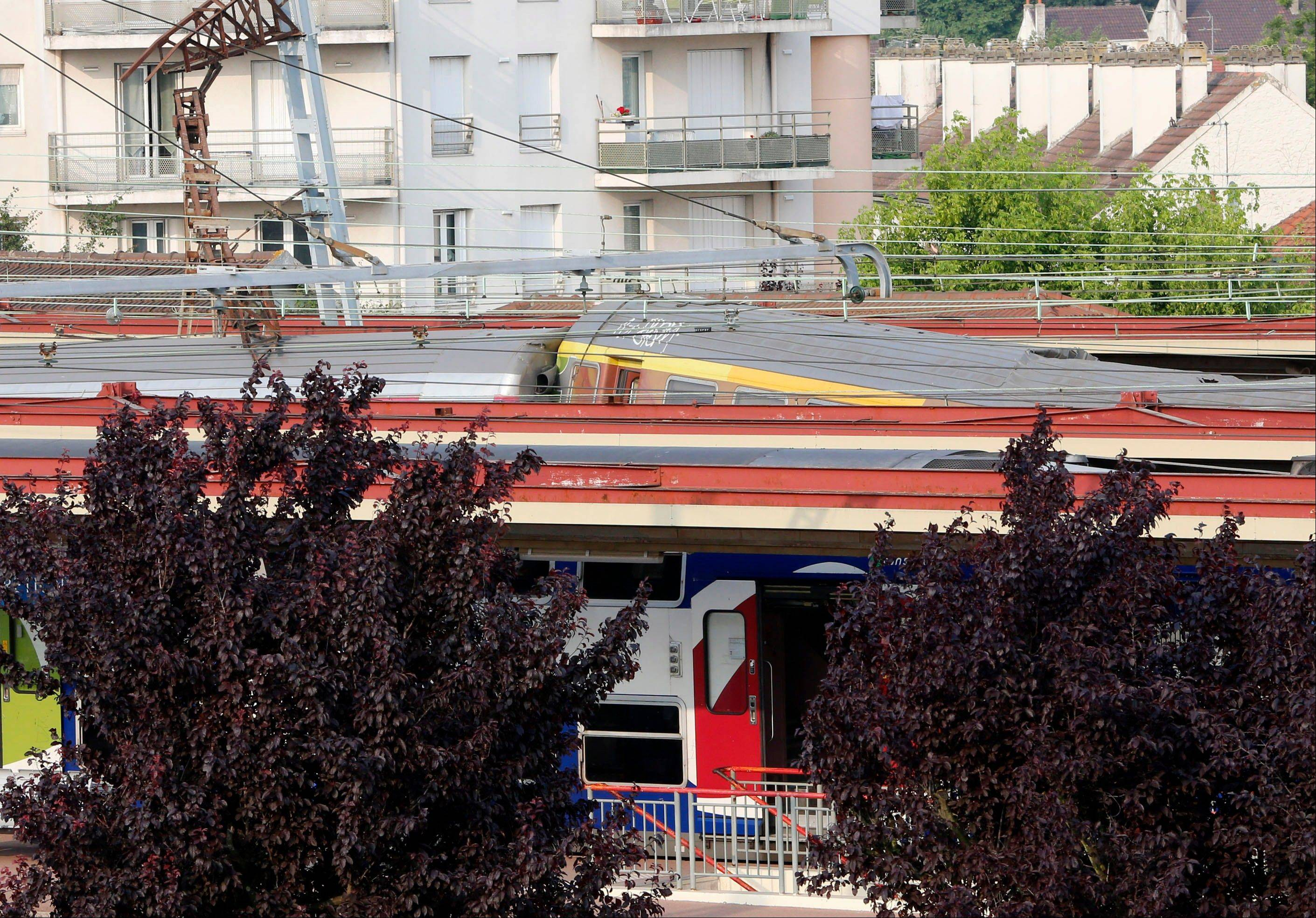 Passenger cars are upturned in a train crash Friday in Bretigny sur Orge, south of Paris. The packed passenger train skidded off its rails after leaving Paris.