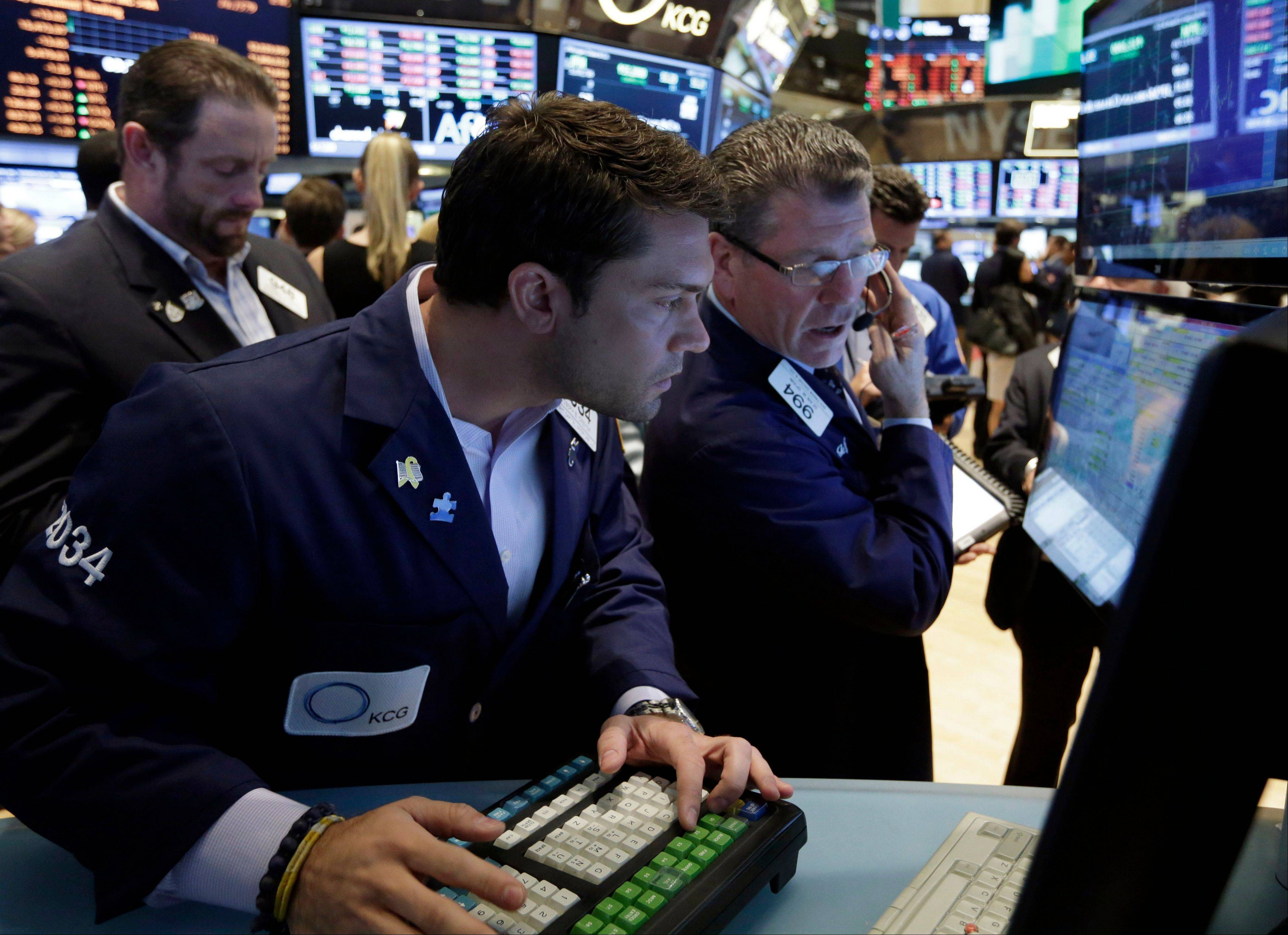 Specialist Joseph Dreyer, center, and trader Sean Spain, right, work Friday on the floor of the New York Stock Exchange.