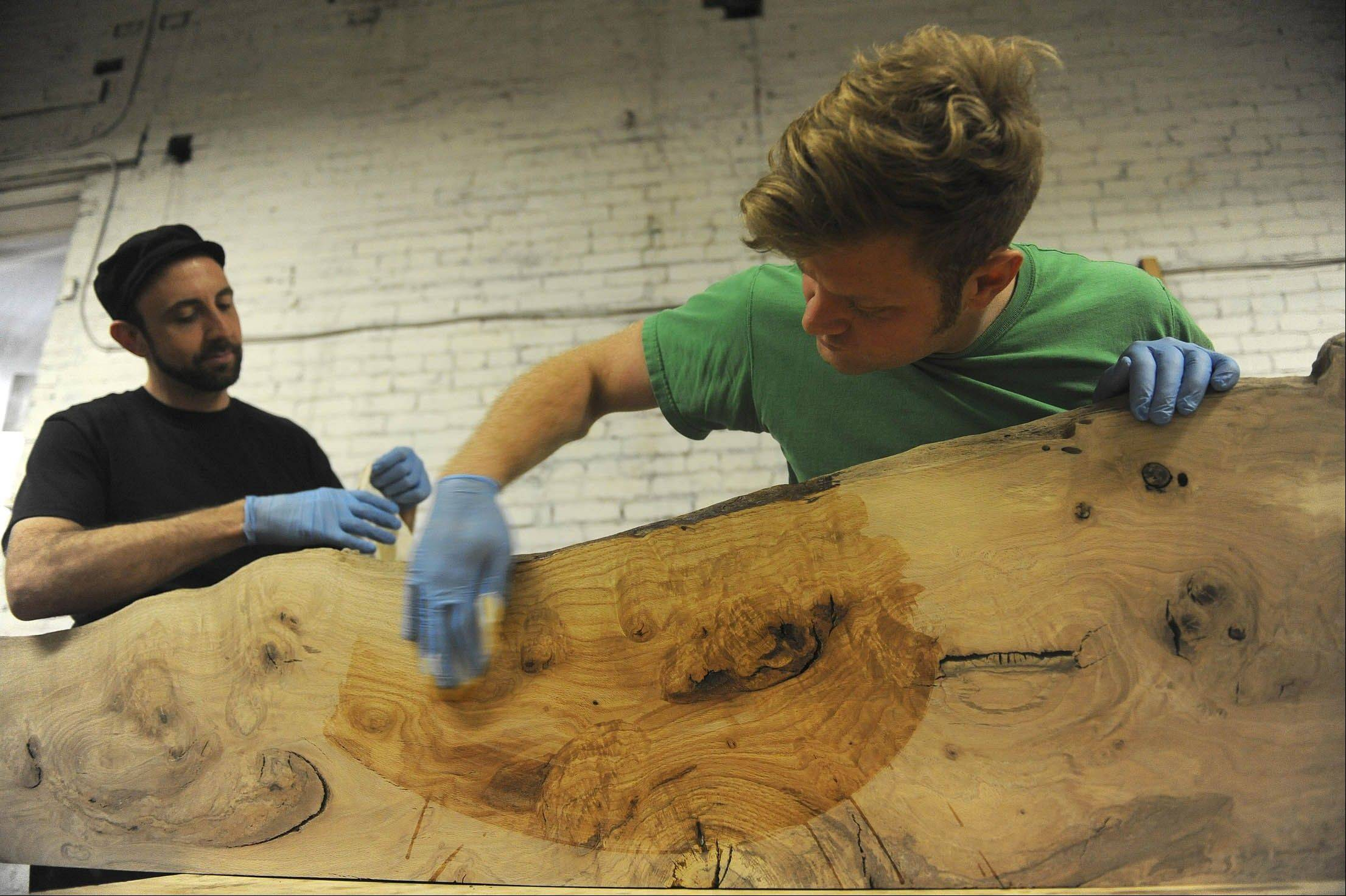 SH13E141RECLAIMEDWOOD May 20, 2013 -- Apprentice Brian McLeod, left, works with Jason Boone of Urban Tree to apply tongue oil to a 12-foot shelf made from pin oak at the wood shop. (SHNS photo by Rebecca Droke / Pittsburgh Post-Gazette) (Newscom TagID: shnsphotos146677.jpg) [Photo via Newscom]