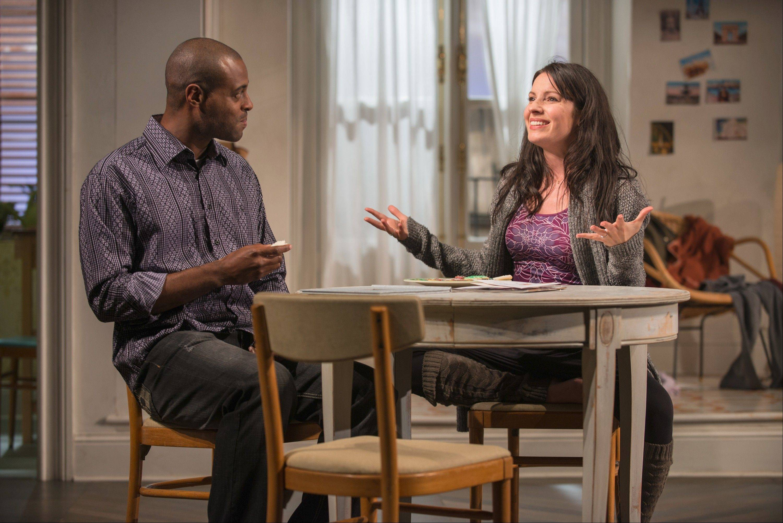 "Abby (Kate Arrington) shares Christmas cookies with her landlord Alioune (Chris Boykin) in Steppenwolf Theatre's Chicago area premiere of ""Belleville,"" Amy Herzog's drama about a couple whose seemingly idyllic life is slowly spiraling out of control."