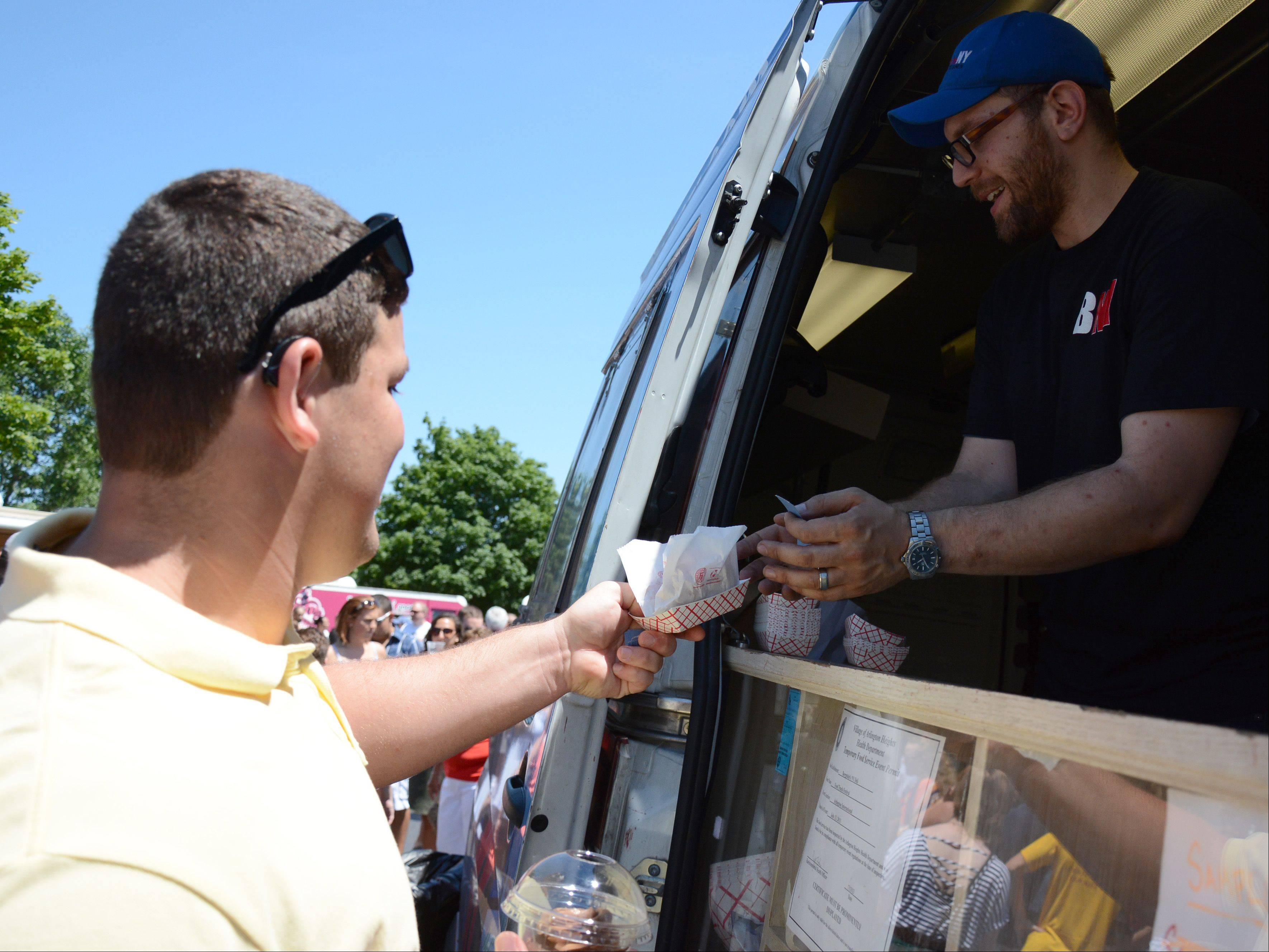 Nick Amren, left, of Crystal Lake, gets a potato pancake from Bill Davis of Bergstein's NY Delicatessen during the Food Truck Festival at Arlington Park on Saturday.