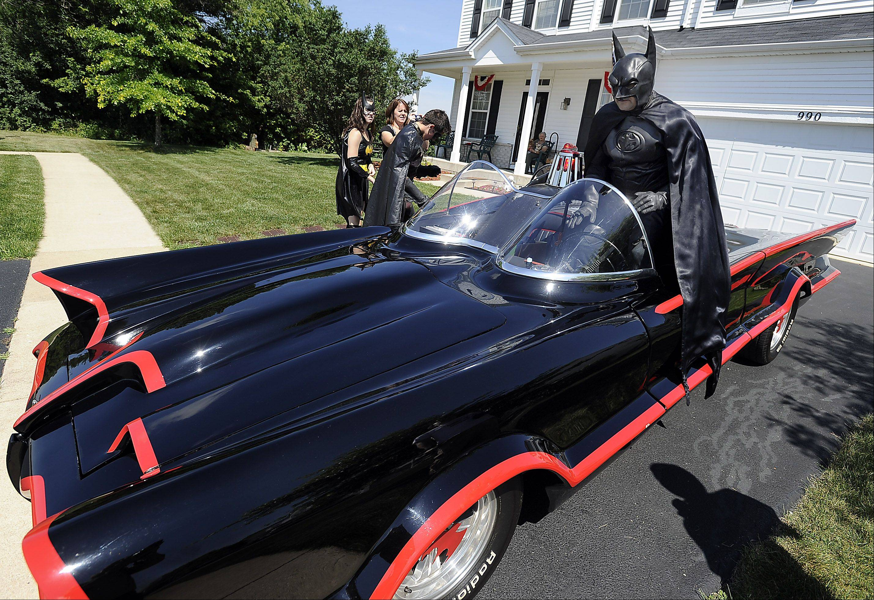 Round Lake Heights Trustee Dominick Mahoney climbs into the Batmobile he just pulled out of the bat cave for the Round Lake Heights Festival Parade on Saturday, July 13.
