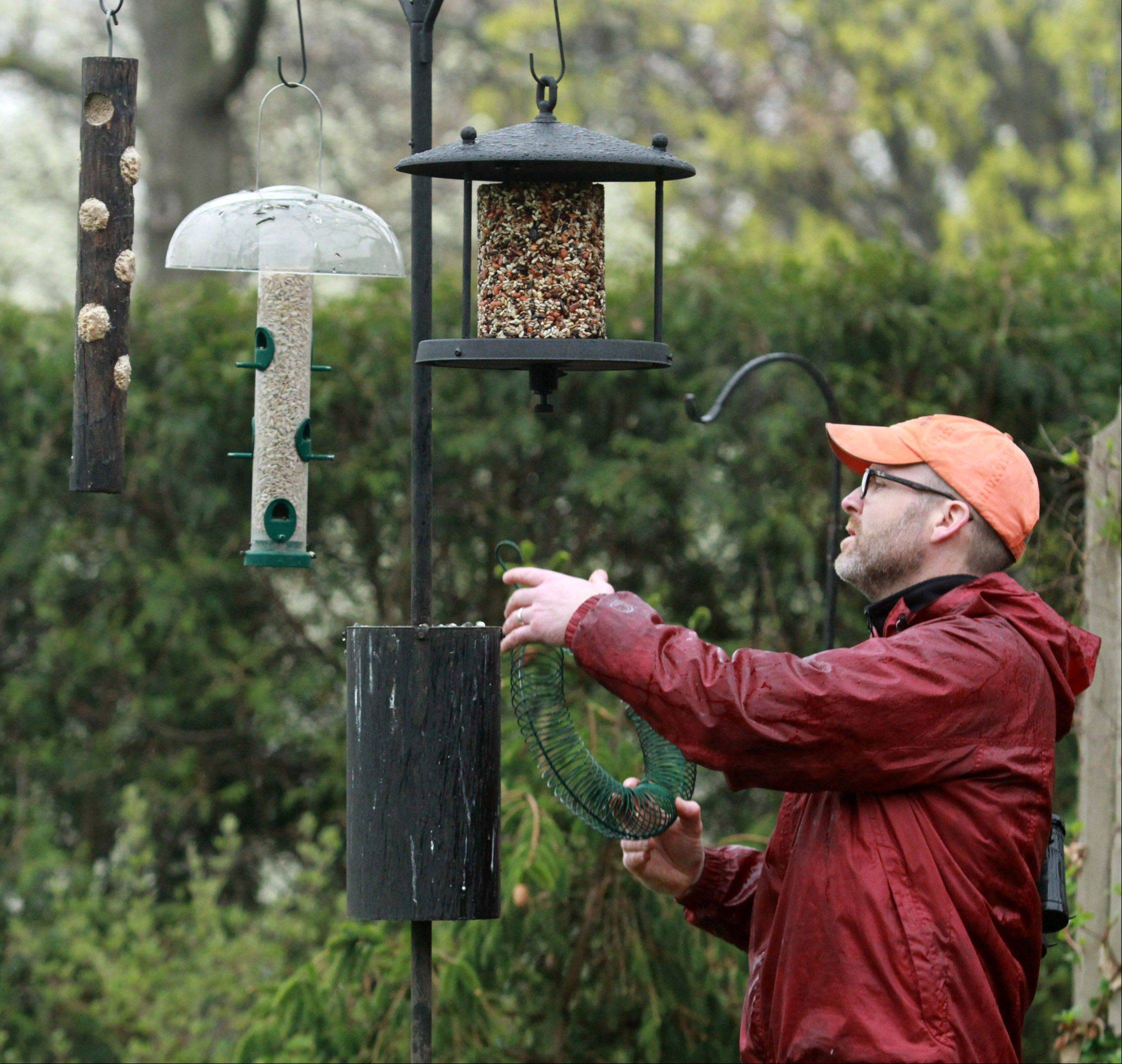 Birdscaper Tim Joyce hangs seed feeders he filled on an advanced pole system in Darlene Schuff's backyard in Highland Park.