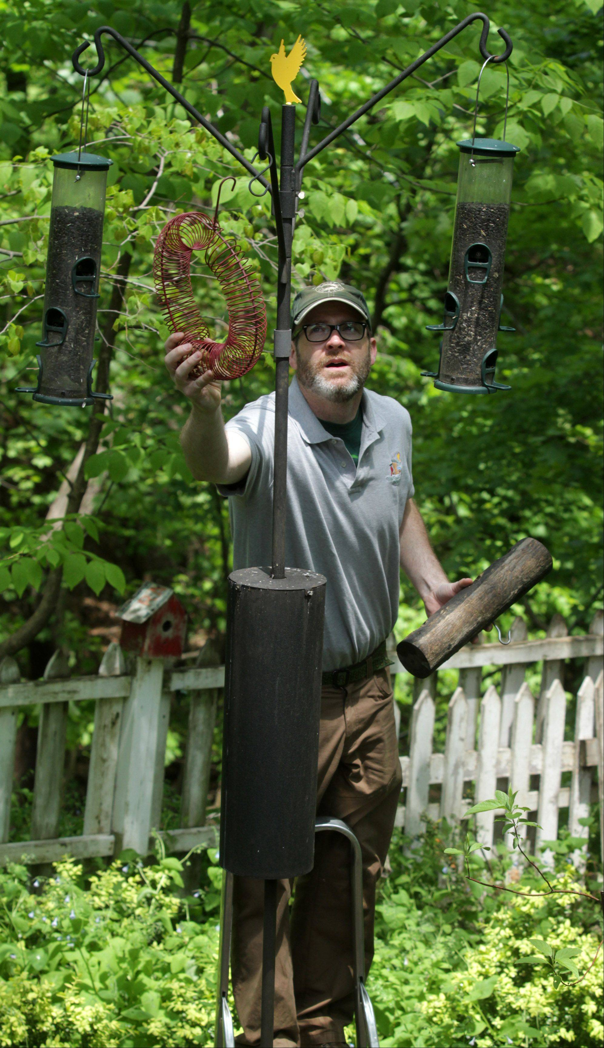 Birdscaper Tim Joyce removes a peanut wreath bird feeder to fill in Darlene Schuff's backyard.