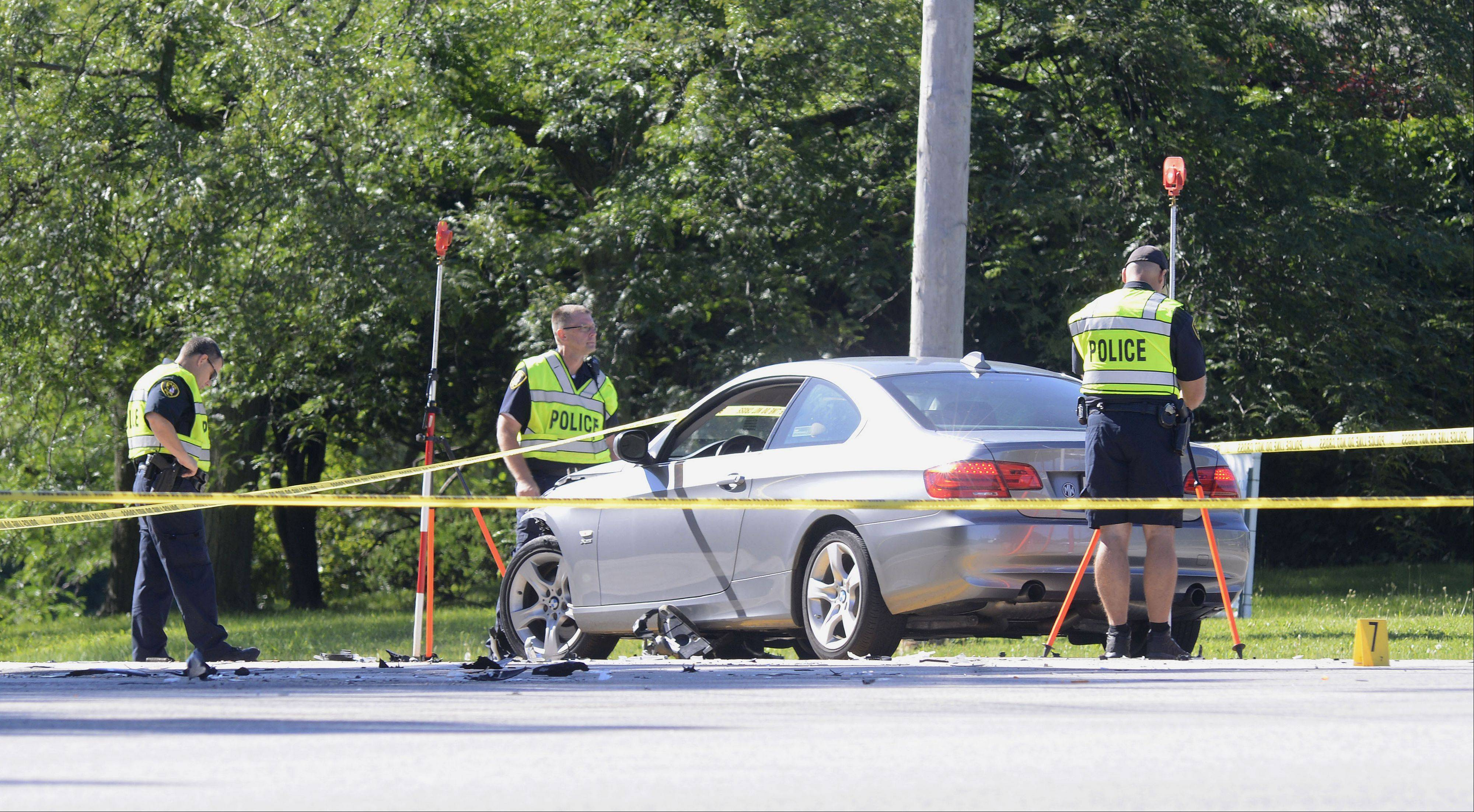 Elgin police take measurements Friday morning at the scene of a car vs. motorcycle crash just east of the intersection of Randall Road and Highland Avenue. Police said a 26-year-old motorcyclist from St. Charles was killed.