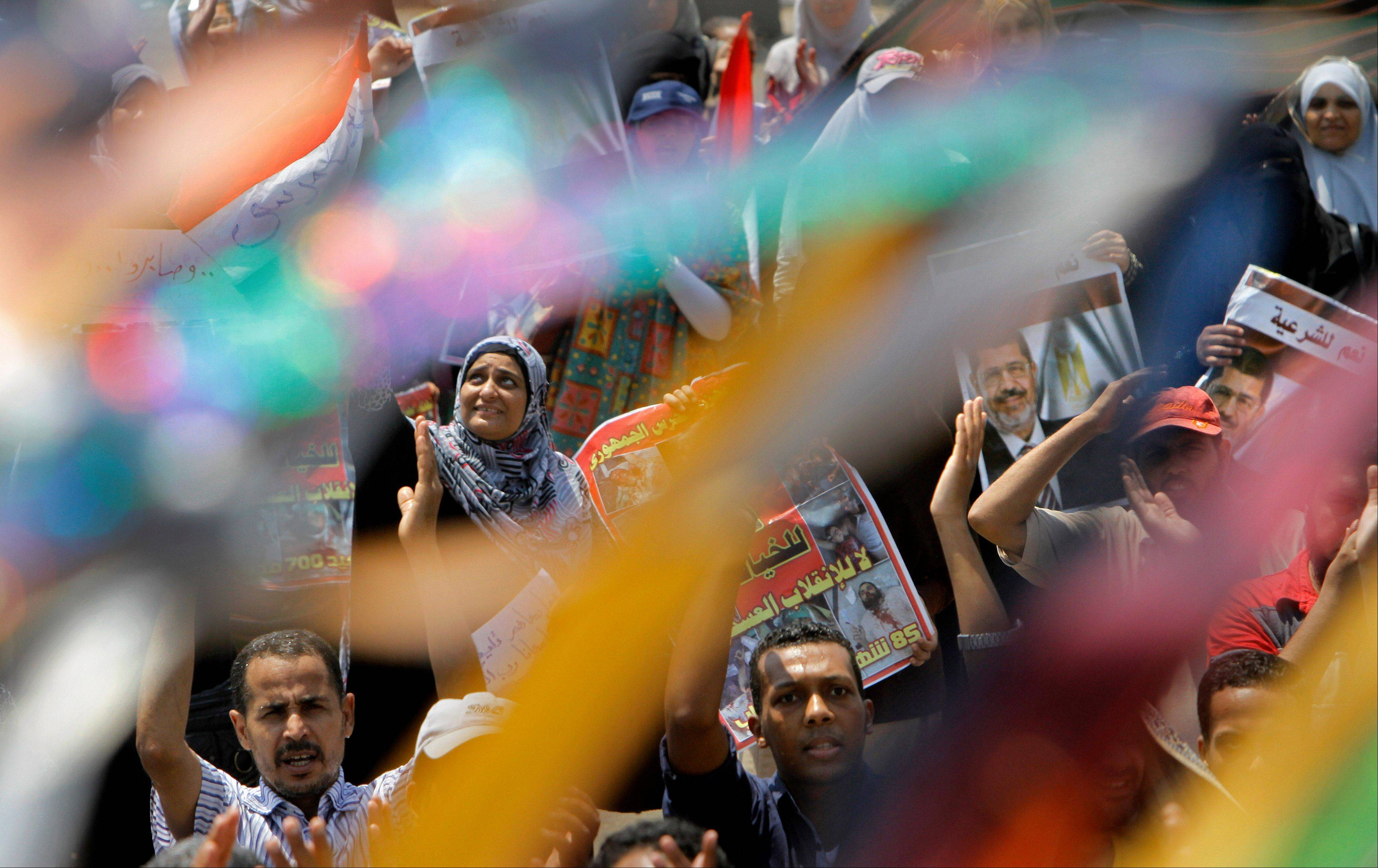 Supporters of Egypt's ousted President Mohammed Morsi hold his posters seen through decorations that mark the Islamic month of Ramadan during a rally near Cairo University, where protesters have installed their camp in Giza, southwest of Cairo, Egypt, Friday, July 12, 2013.