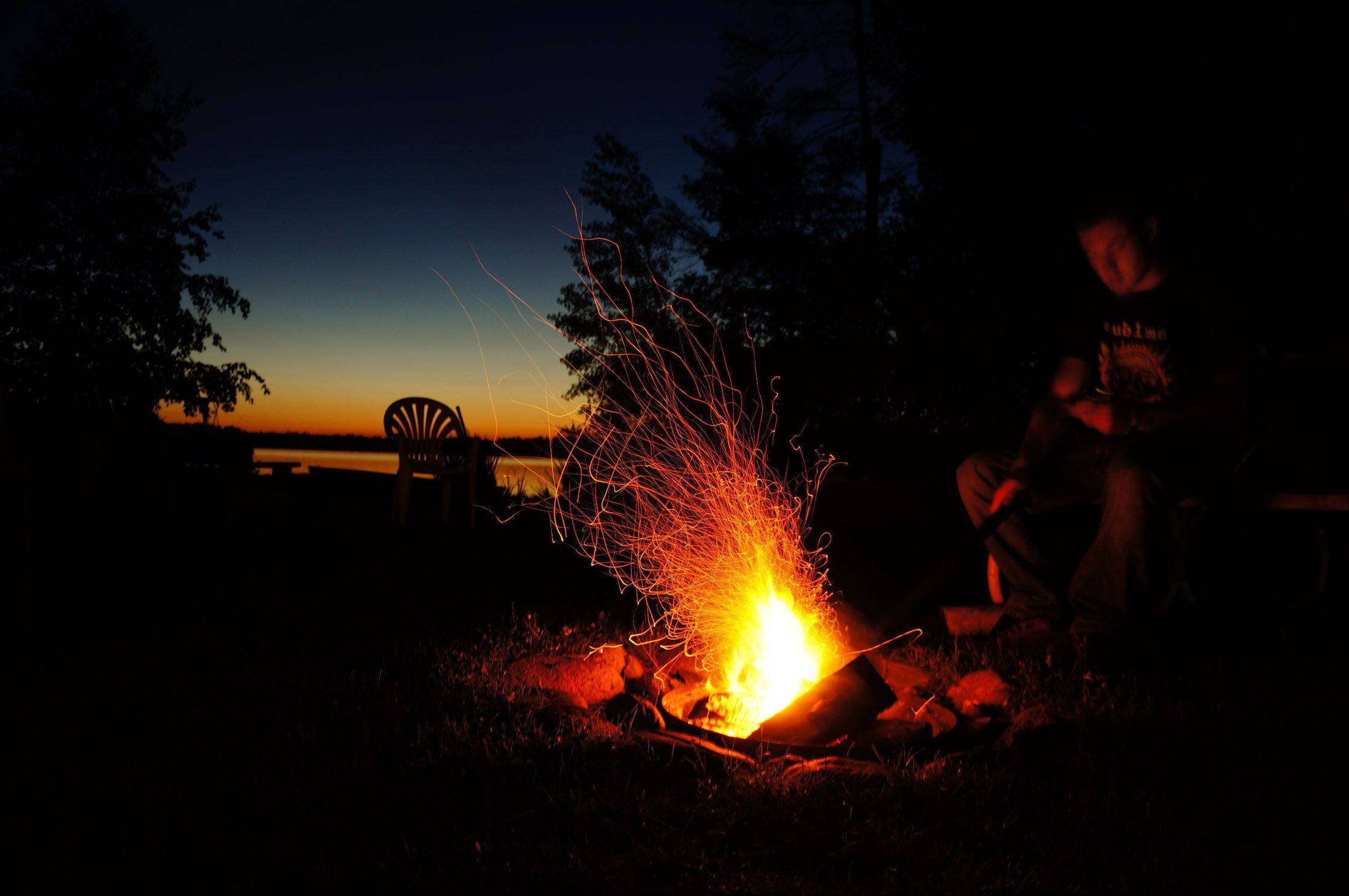 Ryan Morabito sits at a campfire poking at the logs as the sun sets last week in Conover, WI.