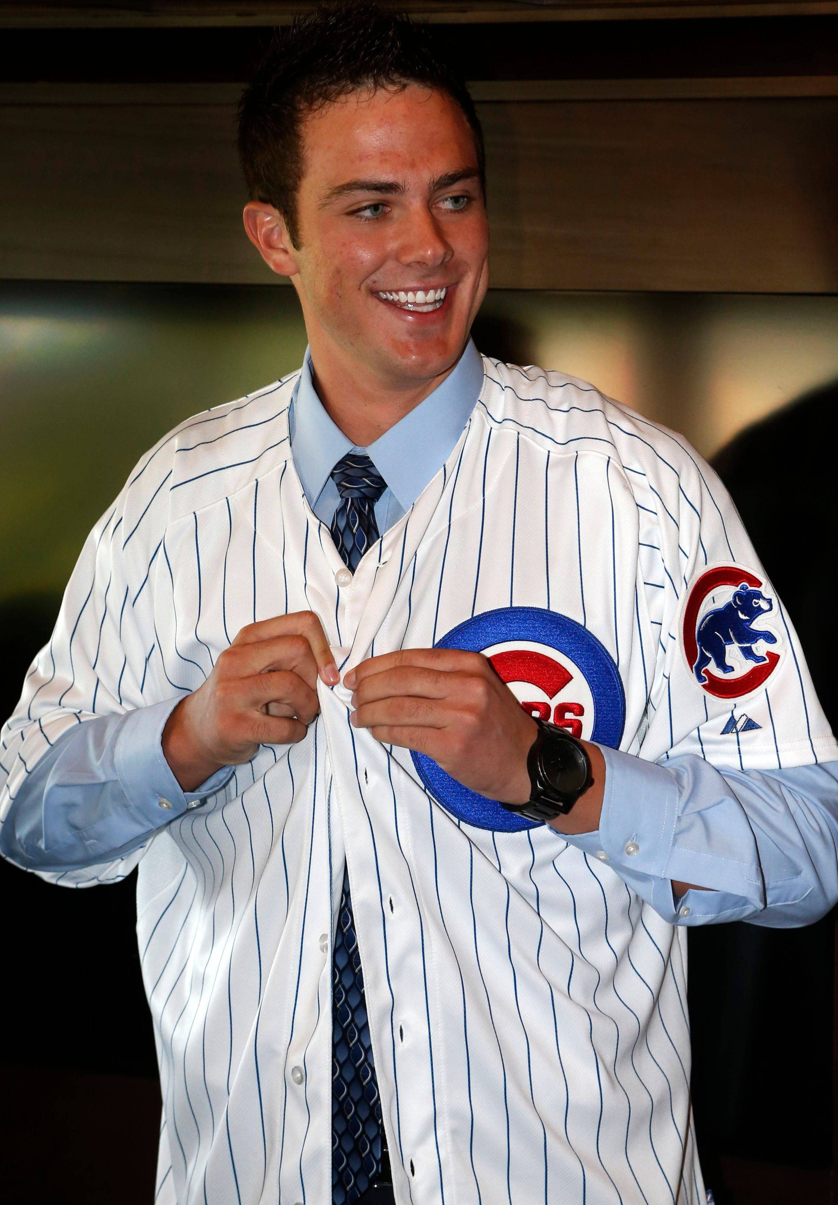 Chicago Cubs' first-round draft pick, third baseman Kris Bryant smiles as he puts on his jersey during a news conference where he was introduced to the media before a baseball game between the Chicago Cubs and the St. Louis Cardinals Friday, July 12 2013, in Chicago.
