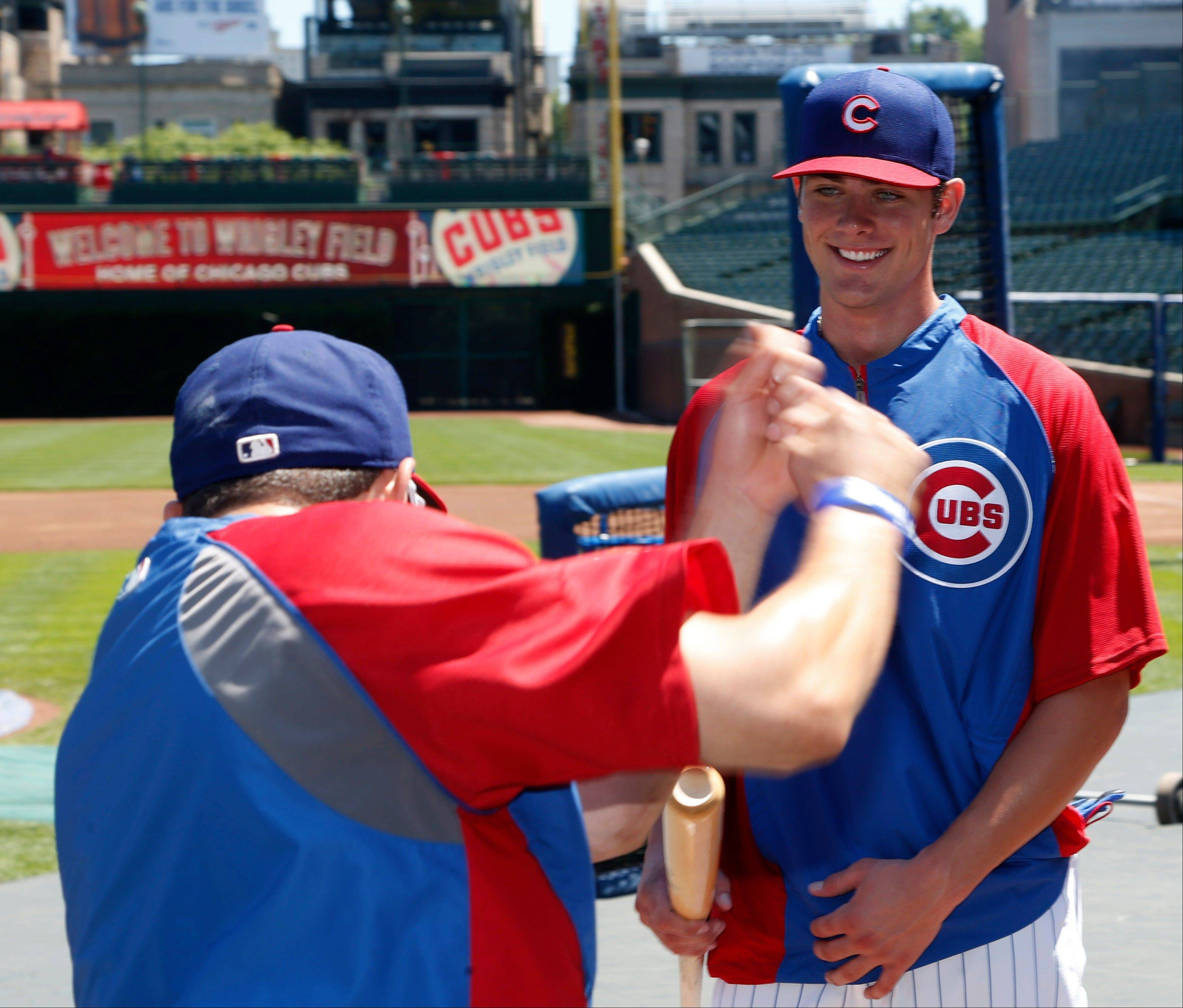 Kris Bryant watches as center fielder David DeJesus talks about batting at Wrigley Field.