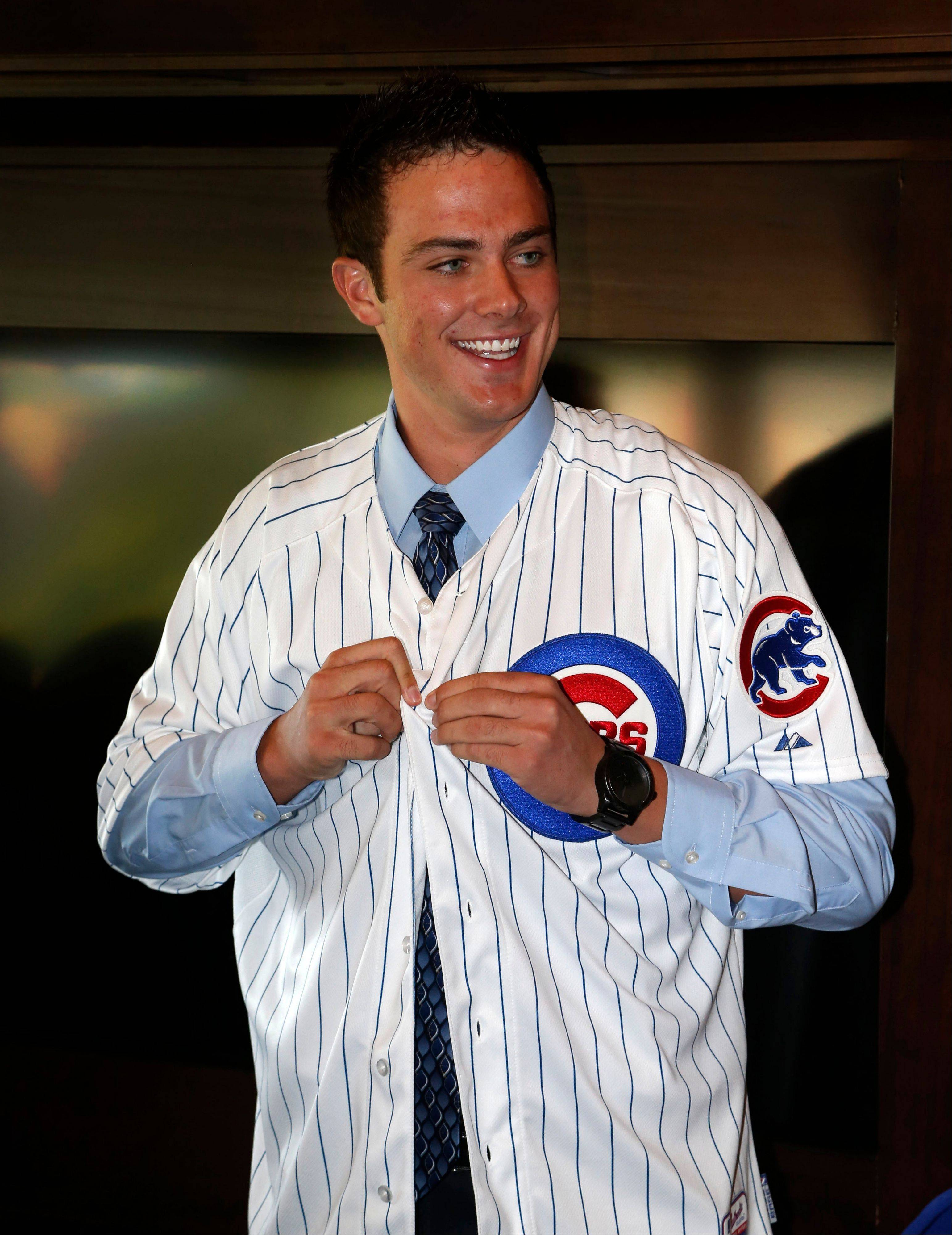 Cubs' first-round draft pick, third baseman Kris Bryant smiles as he puts on his jersey during a news conference where he was introduced to the media before a baseball game between the Chicago Cubs and the St. Louis Cardinals on Friday.