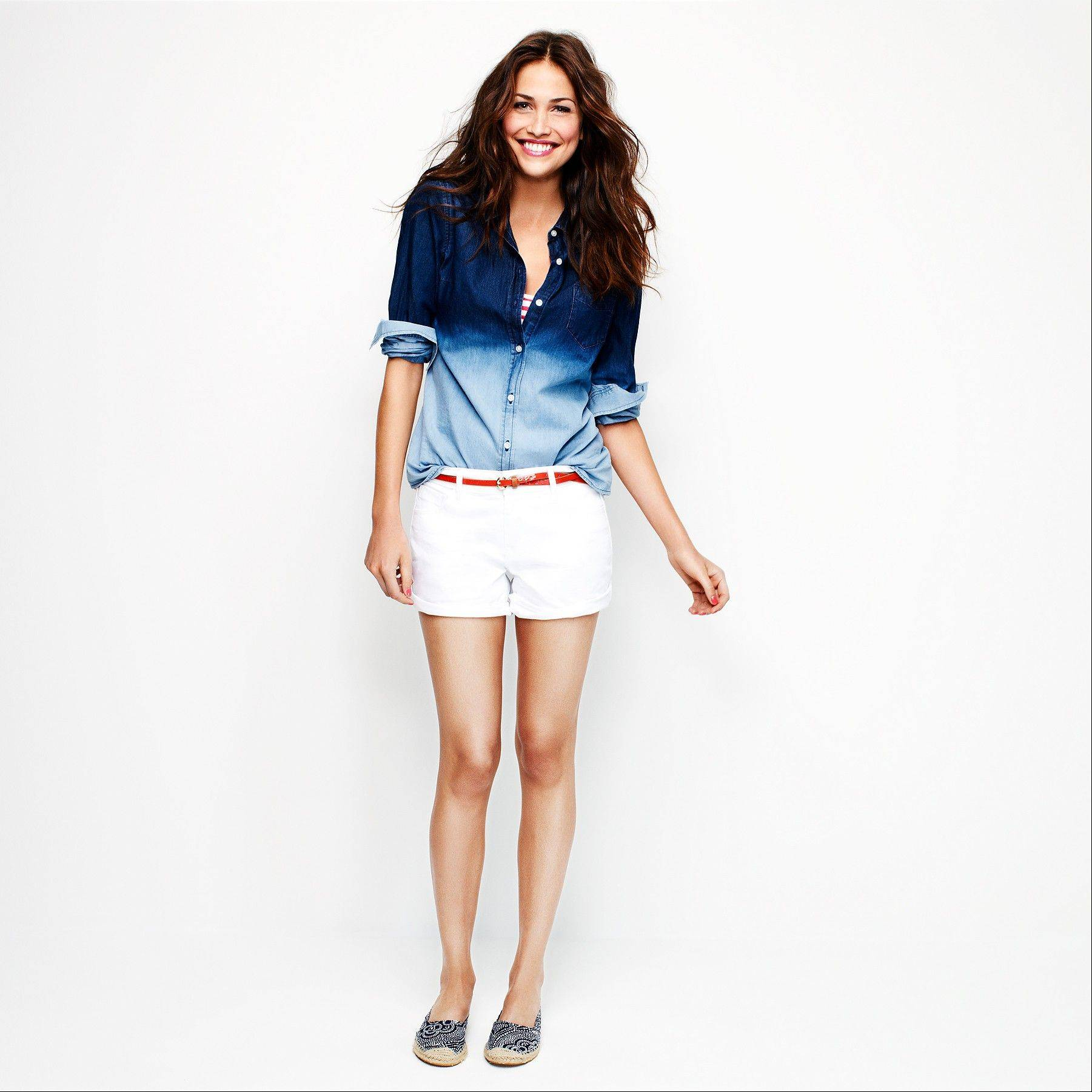 A model wears white denim shorts and a two-tone blue denim top. Many stores are recognizing that shoppers like to purchase their summer clothing when the weather is warm enough for them to wear it.
