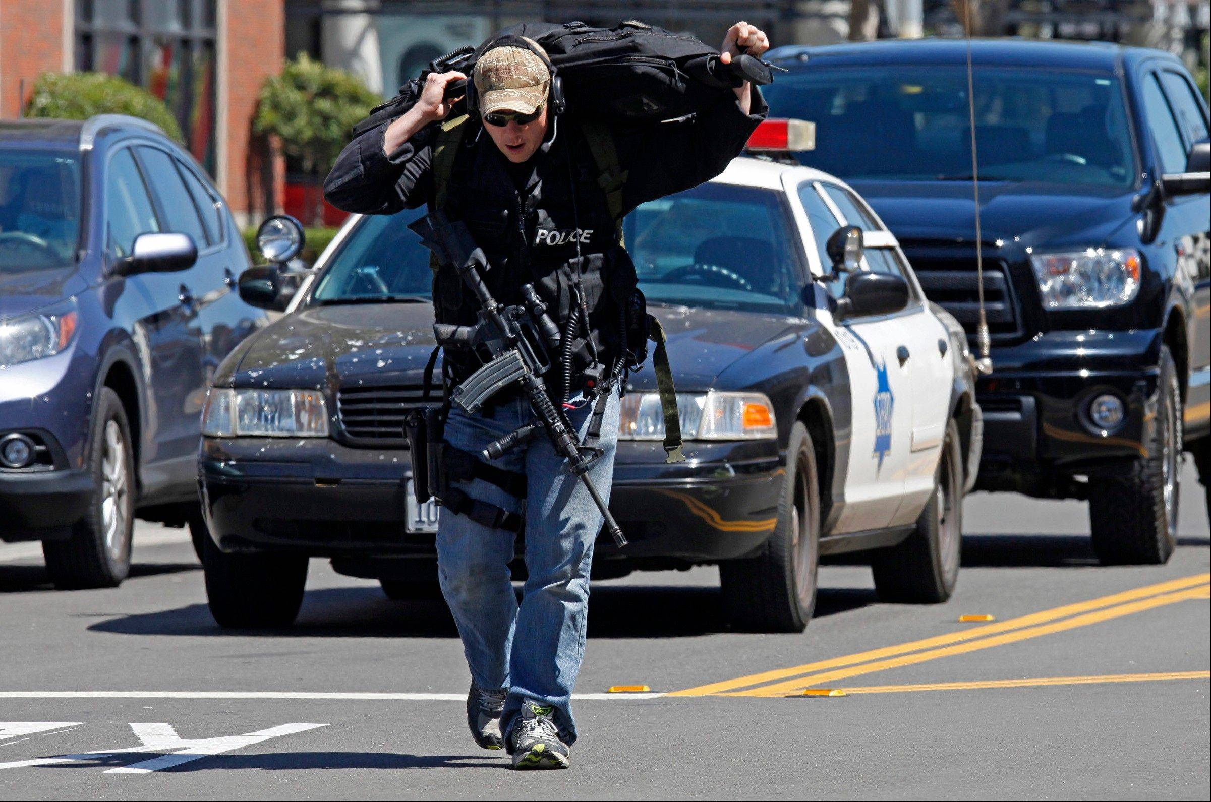 A police officer carries weapons down Eighth Street toward the scene of a shooting Friday in San Francisco.