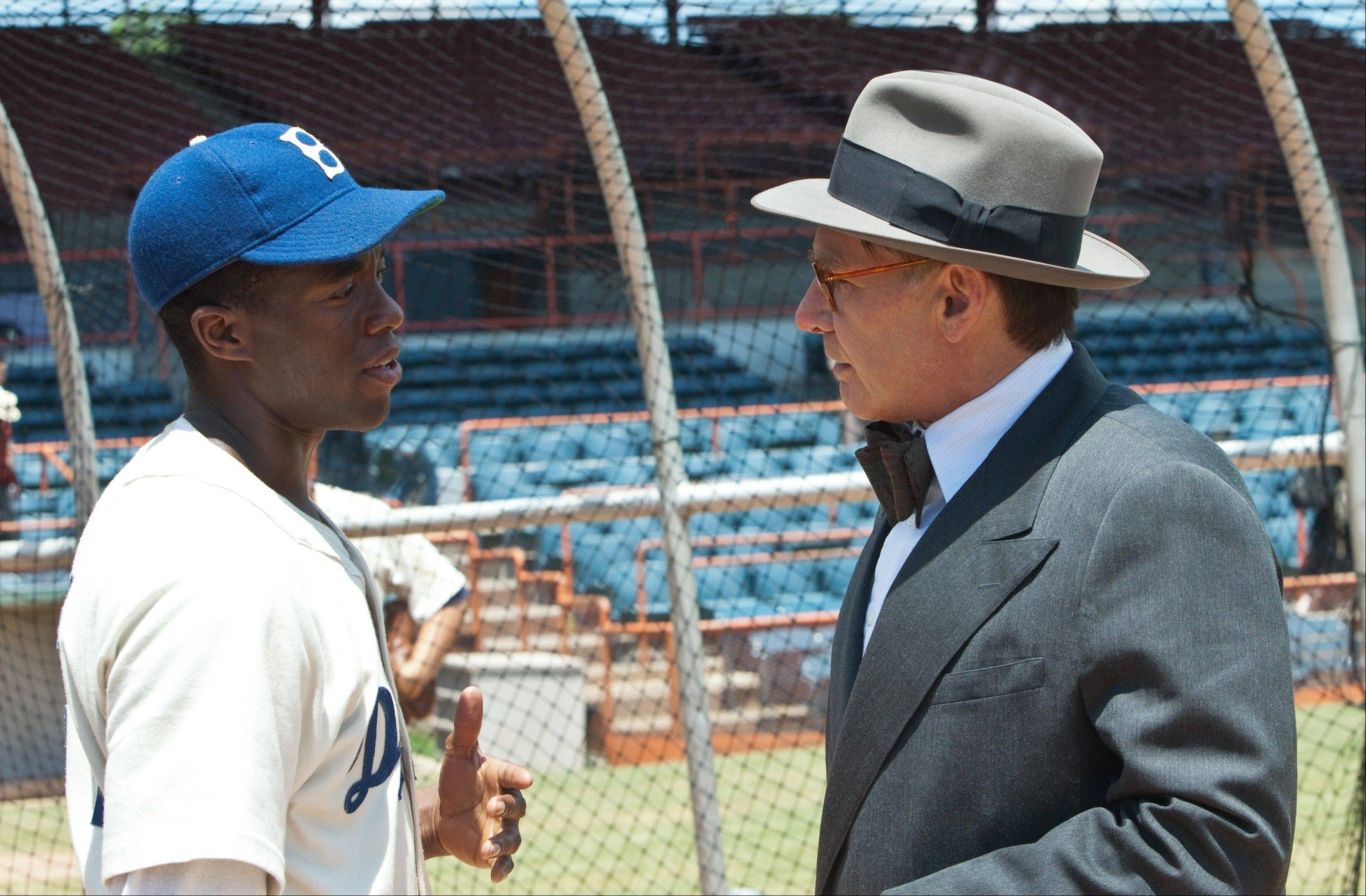"Branch Rickey (Harrison Ford, right) integrates the Brooklyn Dodgers by hiring Jackie Robinson (Chadwick Boseman) in ""42."""