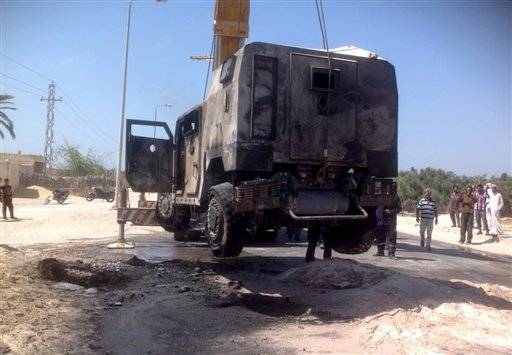 The charred remains of an armored vehicle are loaded onto a trick after a rocket-propelled gre
