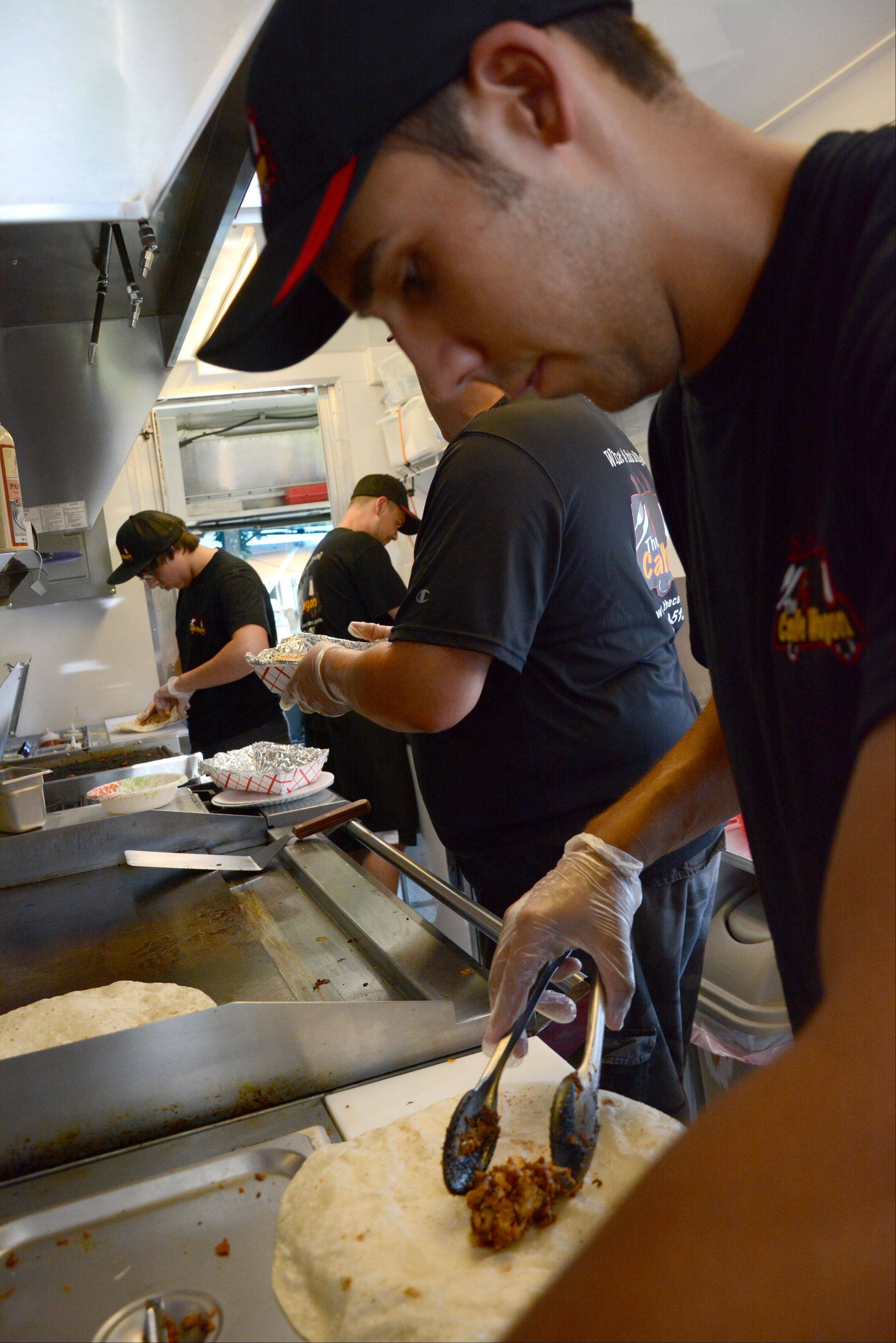 Ryan Oakes, of West Chicago, makes a burrito inside the Calle Wagon during the Food Truck Festival at Arlington Park on Saturday.