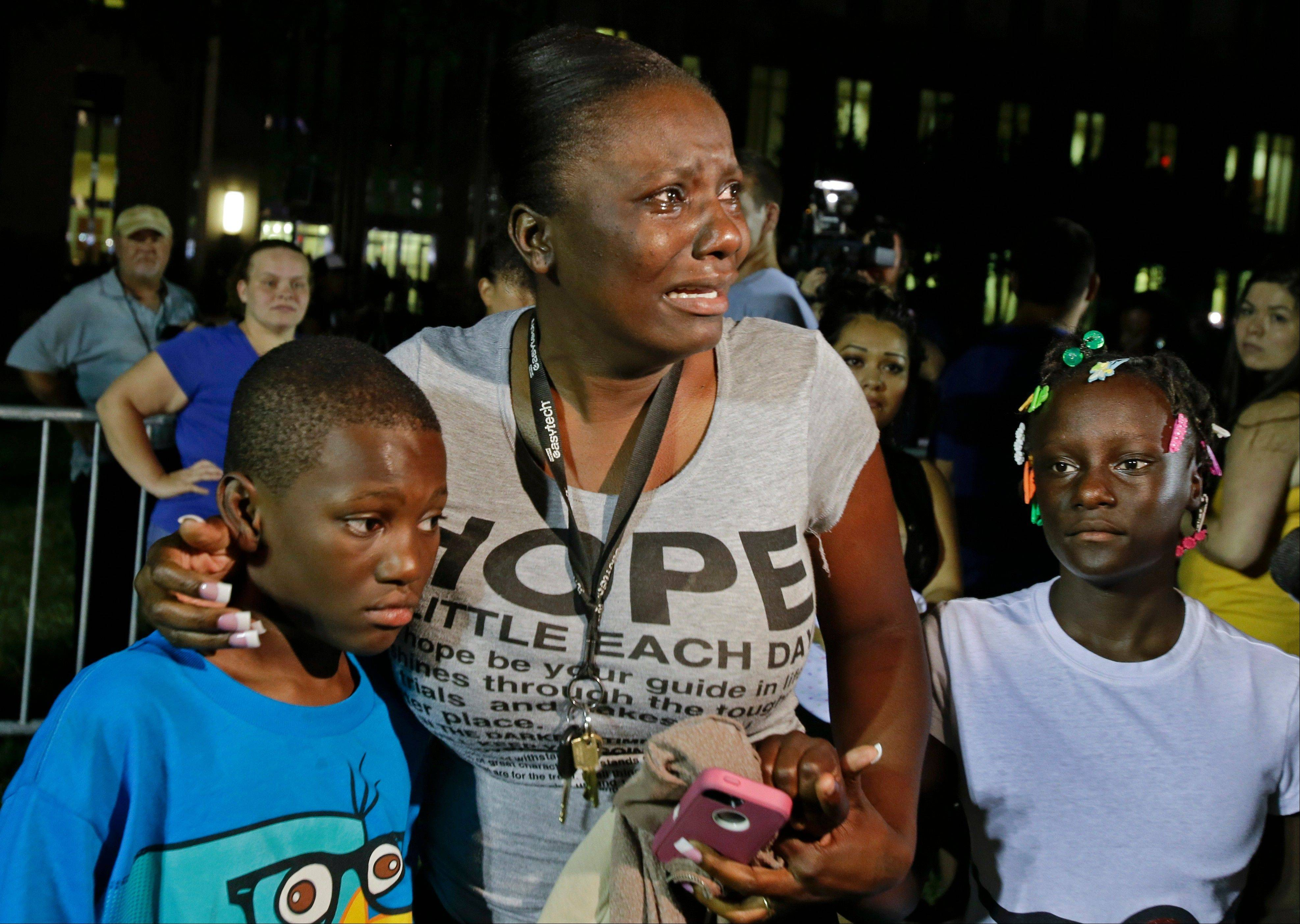 Darrsie Jackson, center, reacts after hearing the verdict of not guilty in the trial of George Zimmerman with her children Linzey Stafford, left, 10, and Shauntina Stafford, 11, at the Seminole County Courthouse, Saturday, July 13, 2013, in Sanford, Fla. Zimmerman had been charged with the 2012 shooting death of 17-year-old Trayvon Martin. Zimmerman, a neighborhood watch volunteer, was cleared of all charges in the shooting of Martin, the unarmed black teenager whose killing unleashed furious debate across the U.S. over racial profiling, self-defense and equal justice.