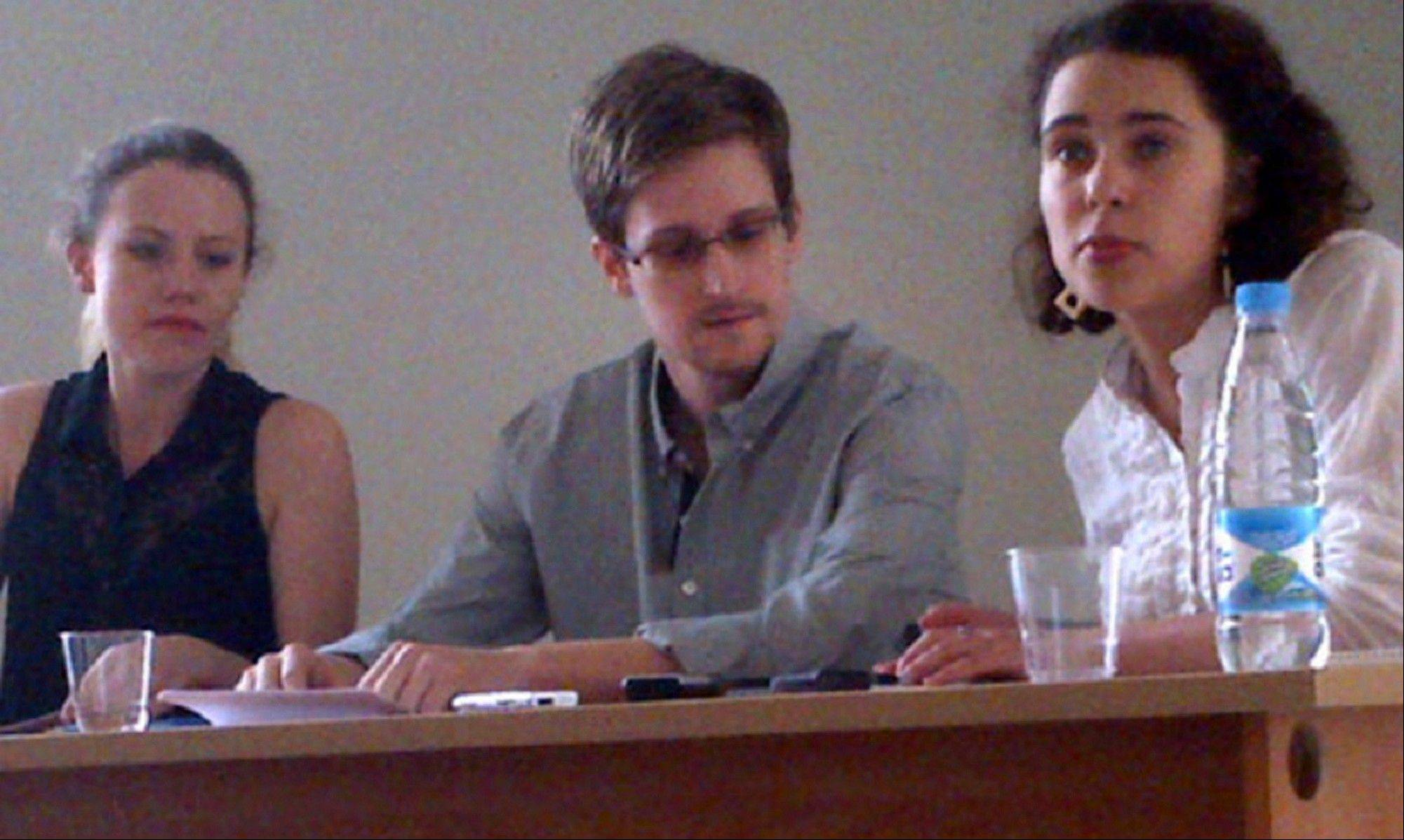 NSA leaker, Edward Snowden, center, attending a press conference Friday at Moscow's Sheremetyevo Airport with Sarah Harrison of WikiLeaks, left. Snowden wants to seek asylum in Russia, according to a Parliament member who was among about a dozen activists and officials to meet with him Friday.
