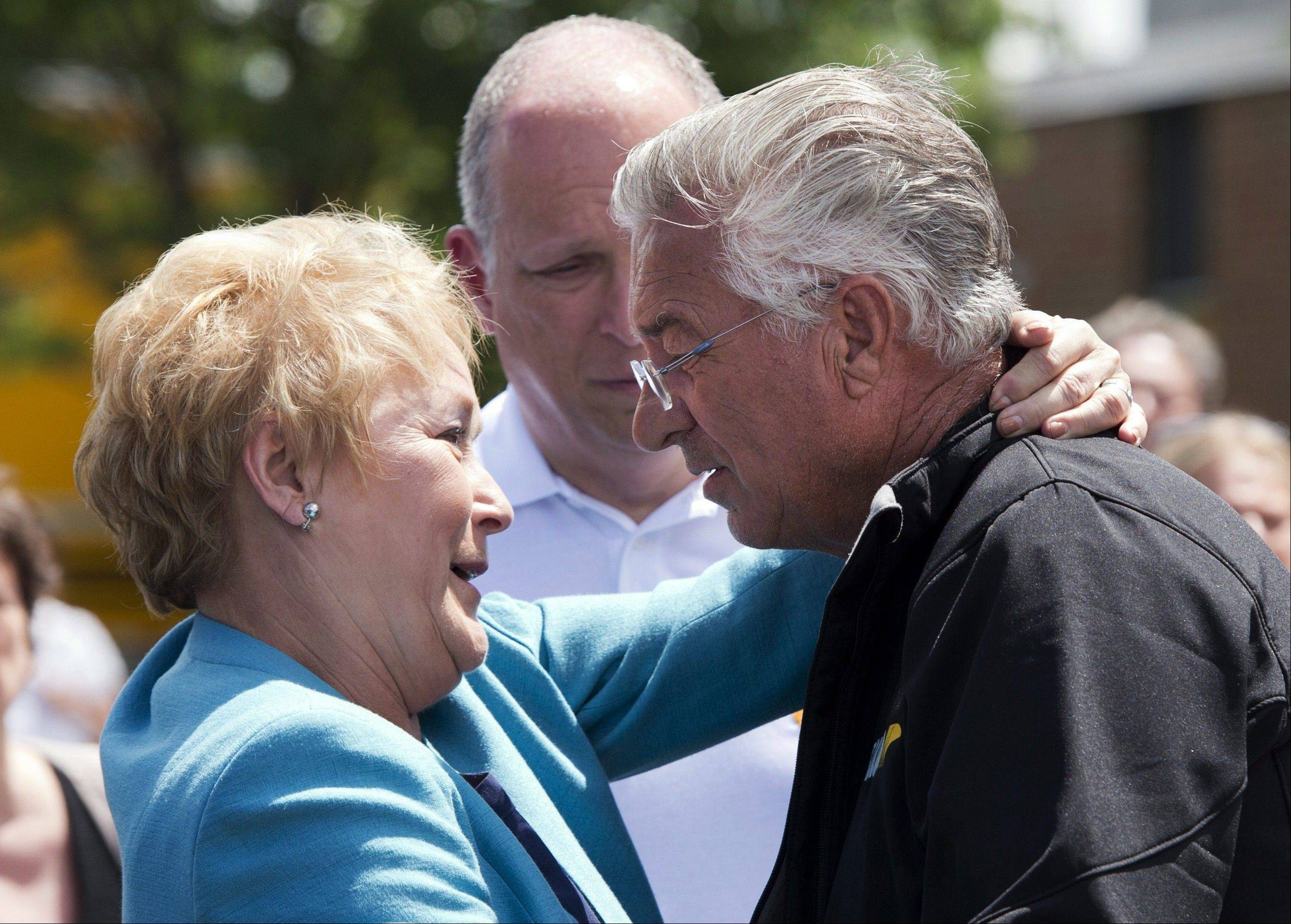 Raymond Lafontaine, who lost his son and two daughters-in-law, receives a hug from Quebec Premier Pauline Marois Friday during her visit to Lac-Megantic, Quebec.