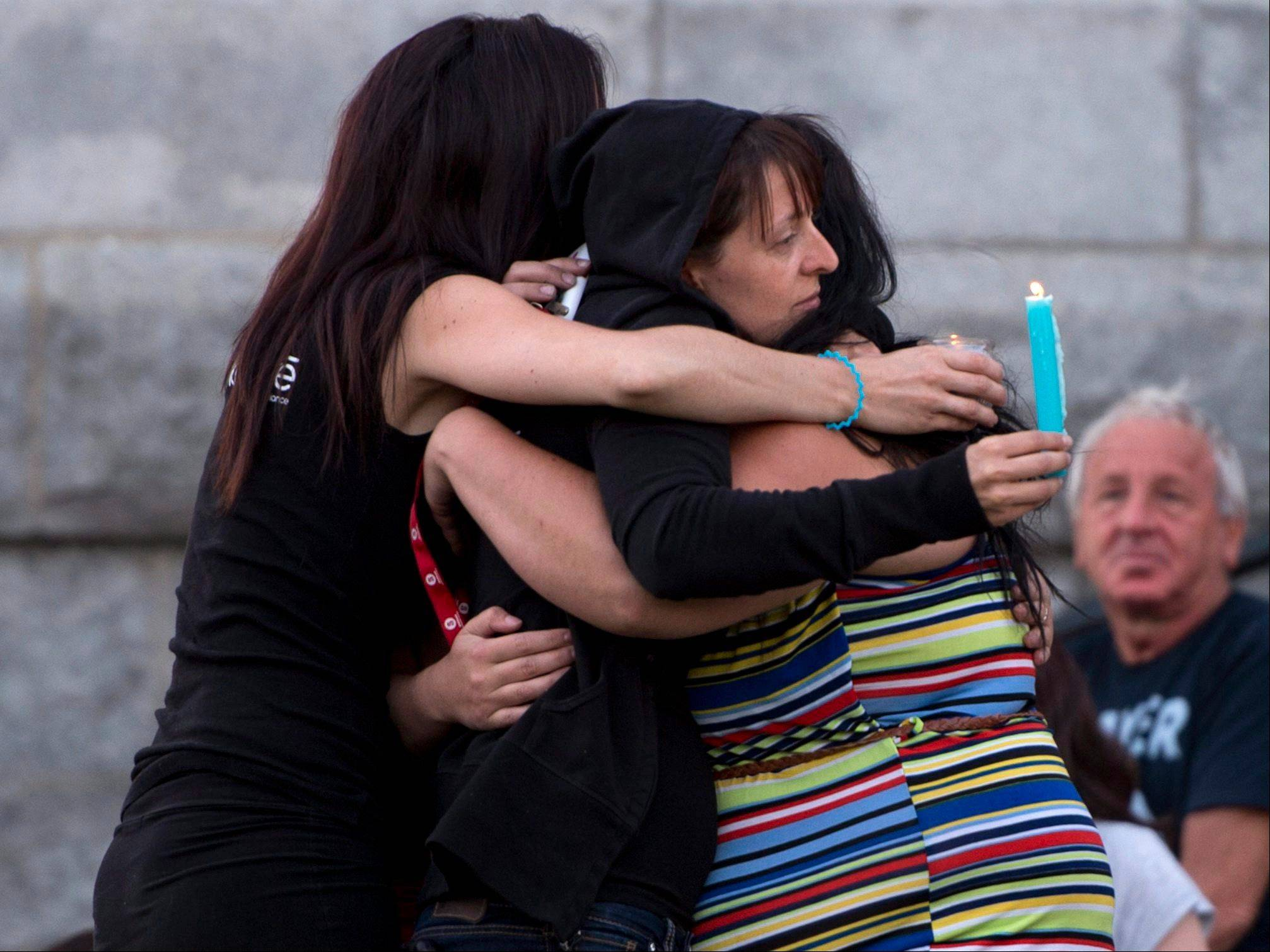 People comfort each other in front of the St-Agnes church Friday during a vigil for the victims of the train crash in Lac-Megantic, Quebec.