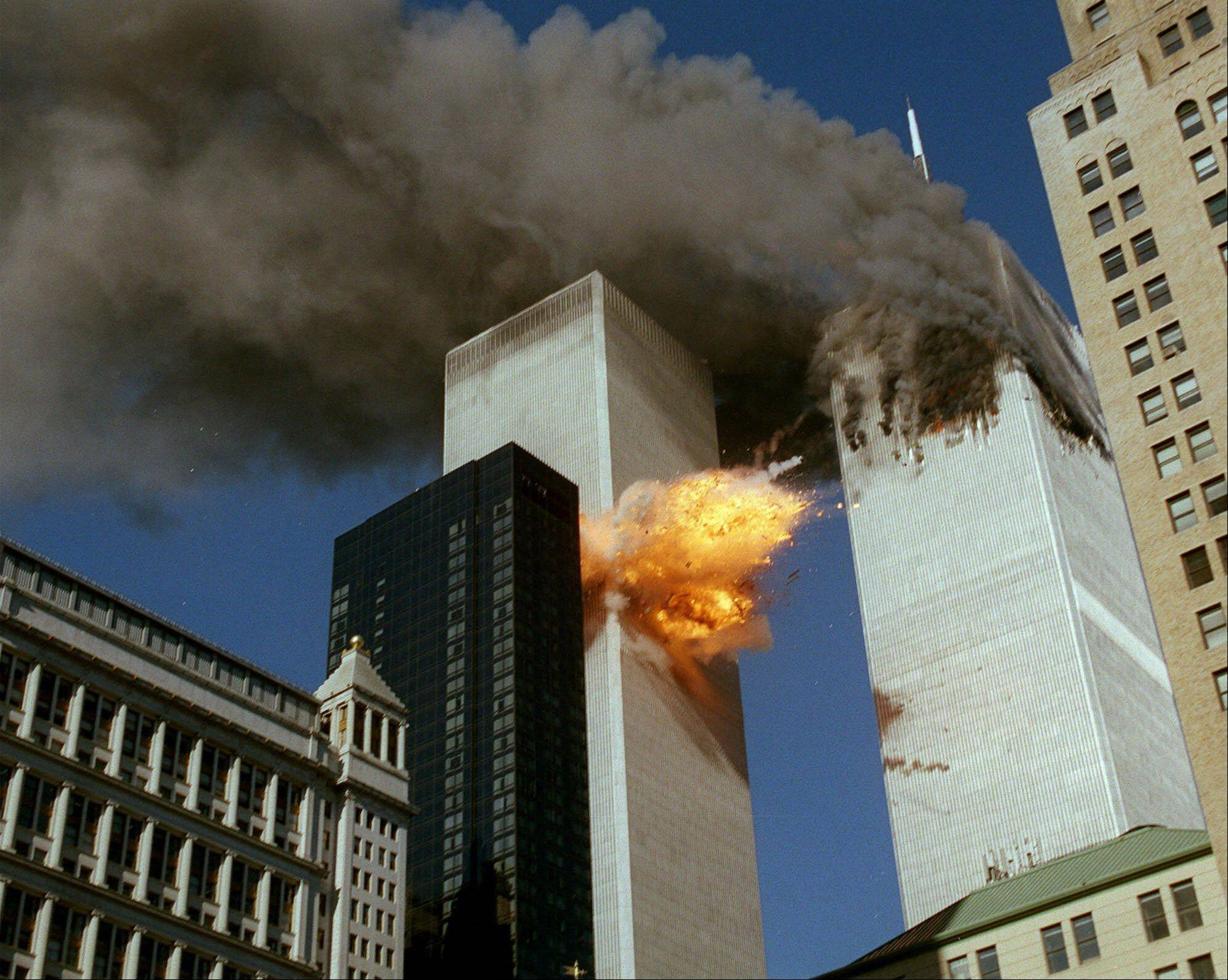 Smoke pours off World Trade Center Tower 1 as flames explode from Tower 2 as it is struck by American Airlines Flight 175, after terrorists crashed hijacked airliners into the buildings.