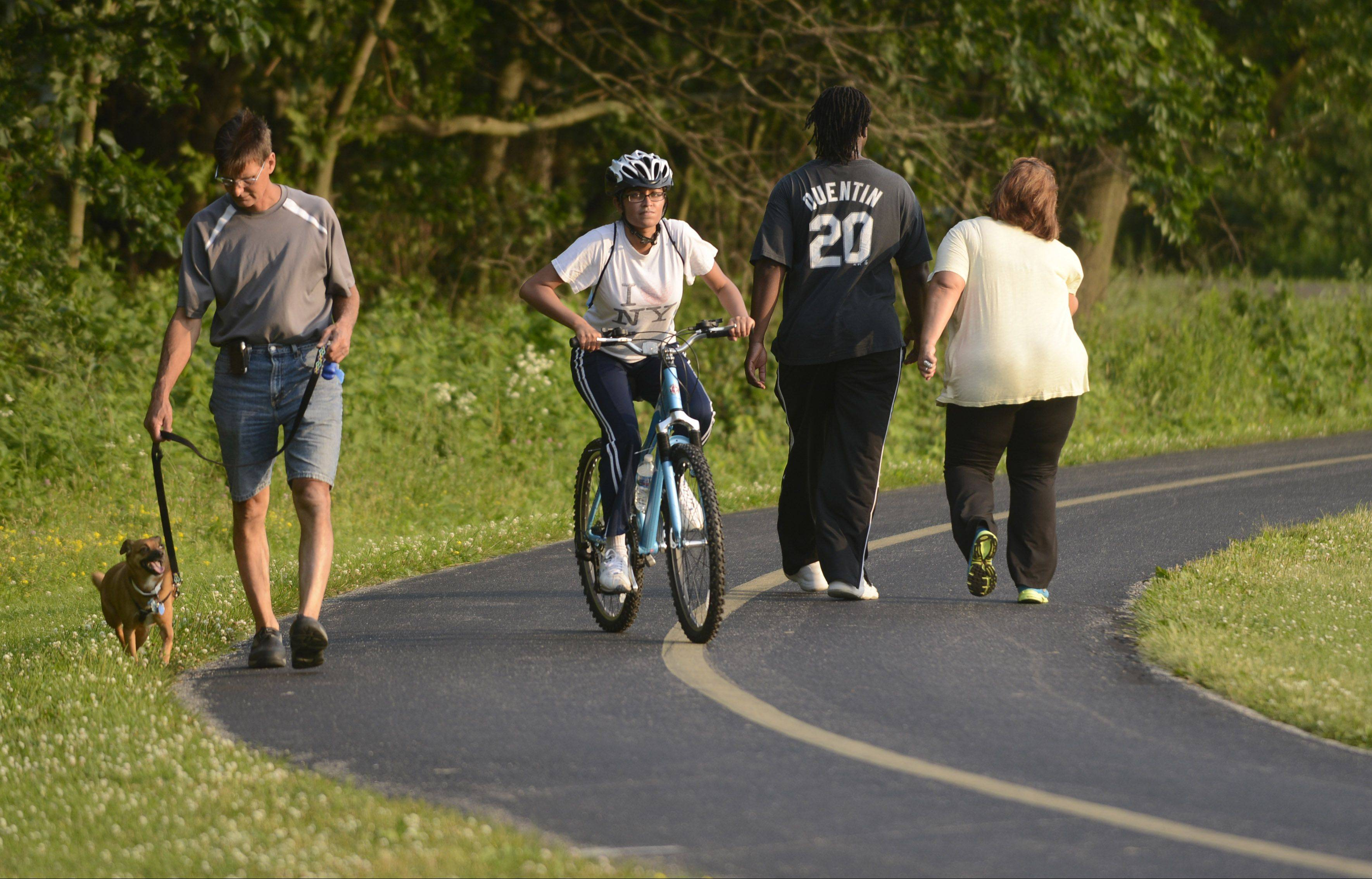 A cyclist slows to ride past pedestrians on the Busse Woods bike path. Trail advocates list simple courtesy as a top way to peacefully coexist and stay safe on the trails.