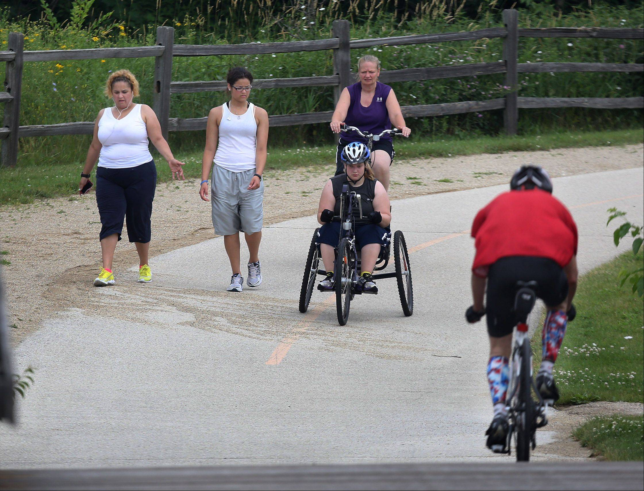 Walkers Sheila Avila, left, and Lizzette Saenz, both of Park City, try to avoid several bicyclists as they share the paths Tuesday in Independence Grove Forest Preserve near Libertyville. Bicycle and walking safety concerns have arisen after several serious accidents have occurred over the summer.